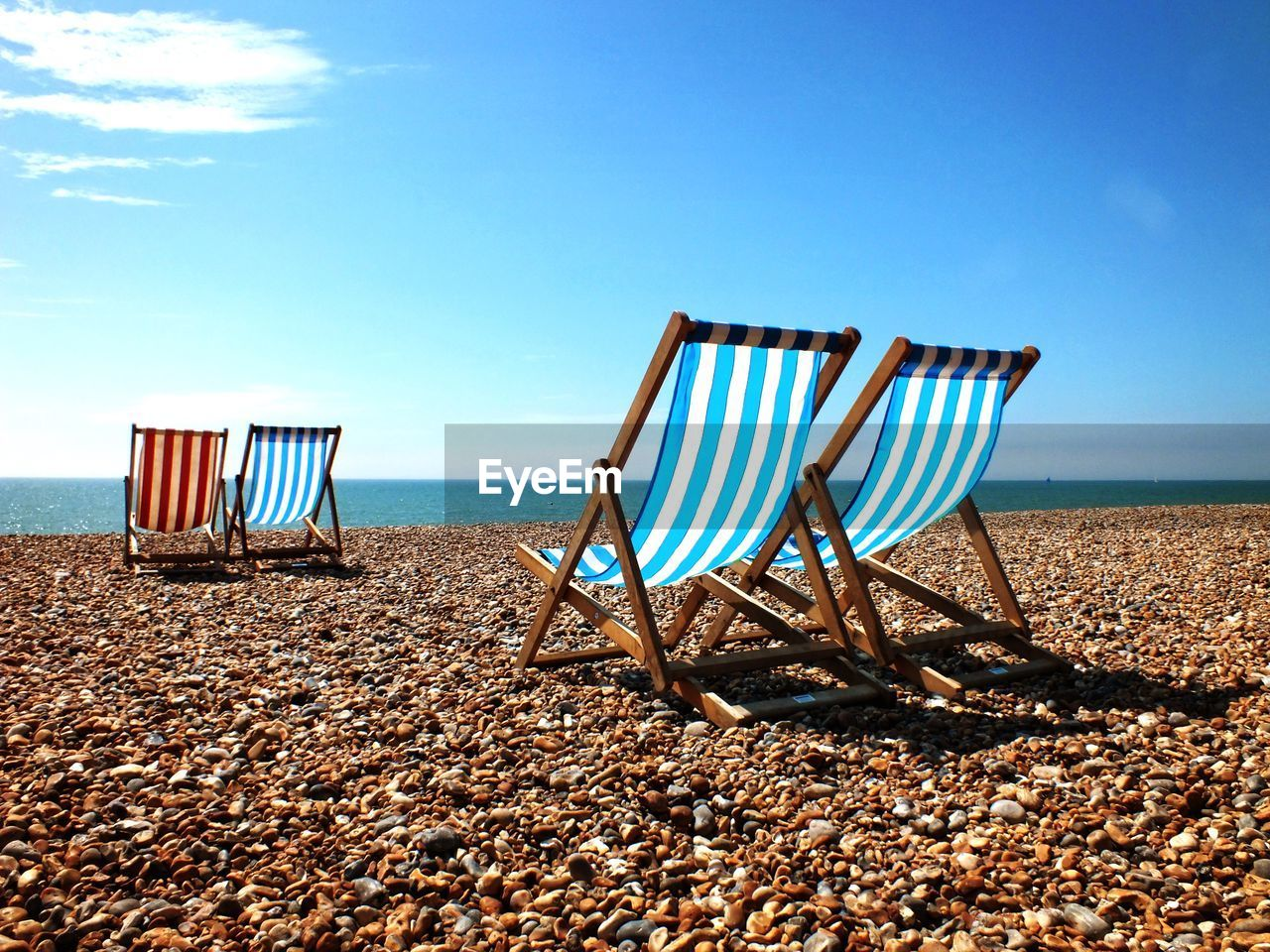 View of deck chairs on coast
