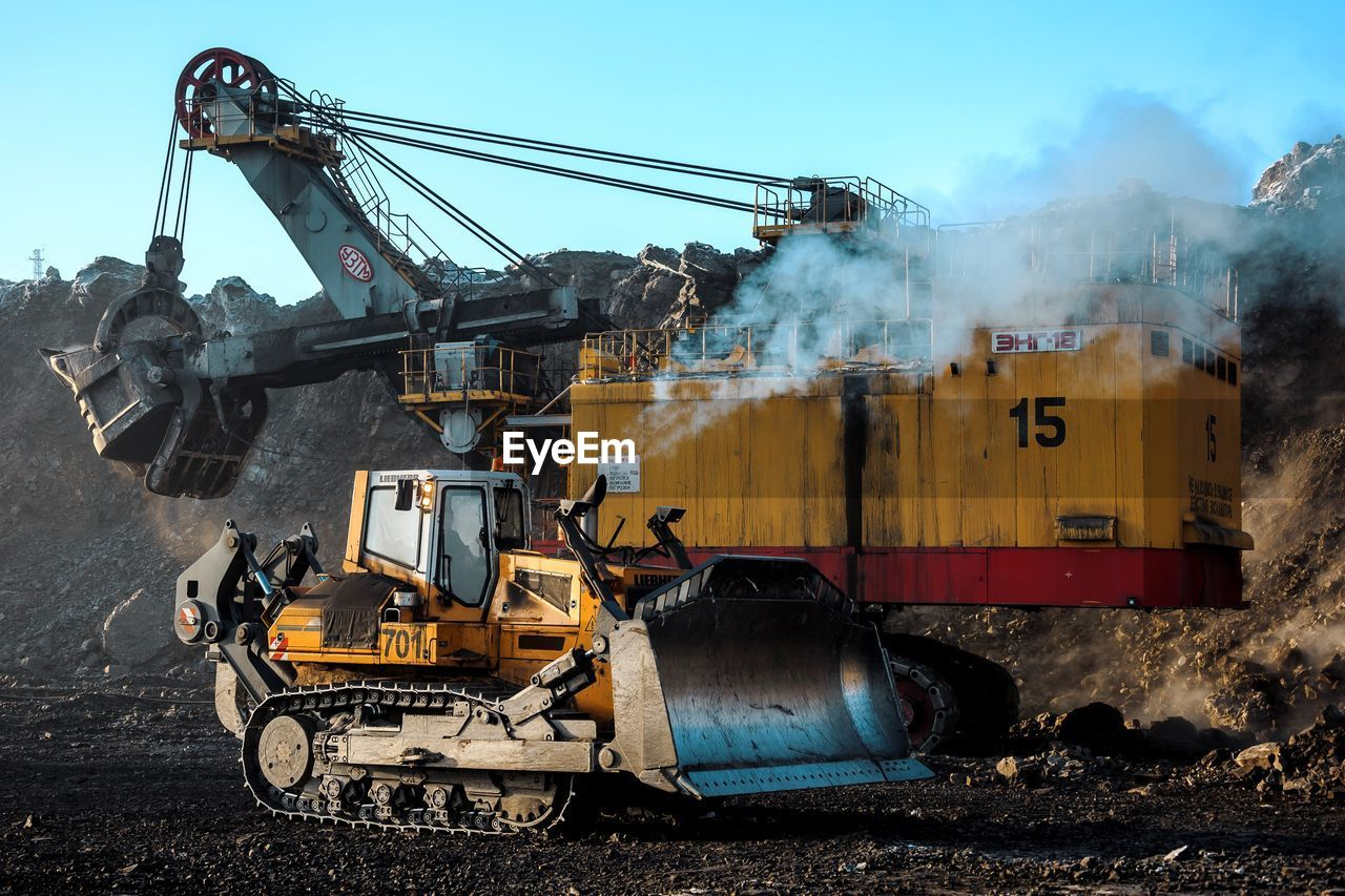 construction industry, construction machinery, industry, machinery, mode of transportation, transportation, day, earth mover, construction site, smoke - physical structure, land vehicle, nature, development, sky, outdoors, bulldozer, no people, pollution, land, dirt, dust, industrial equipment, air pollution, quarry