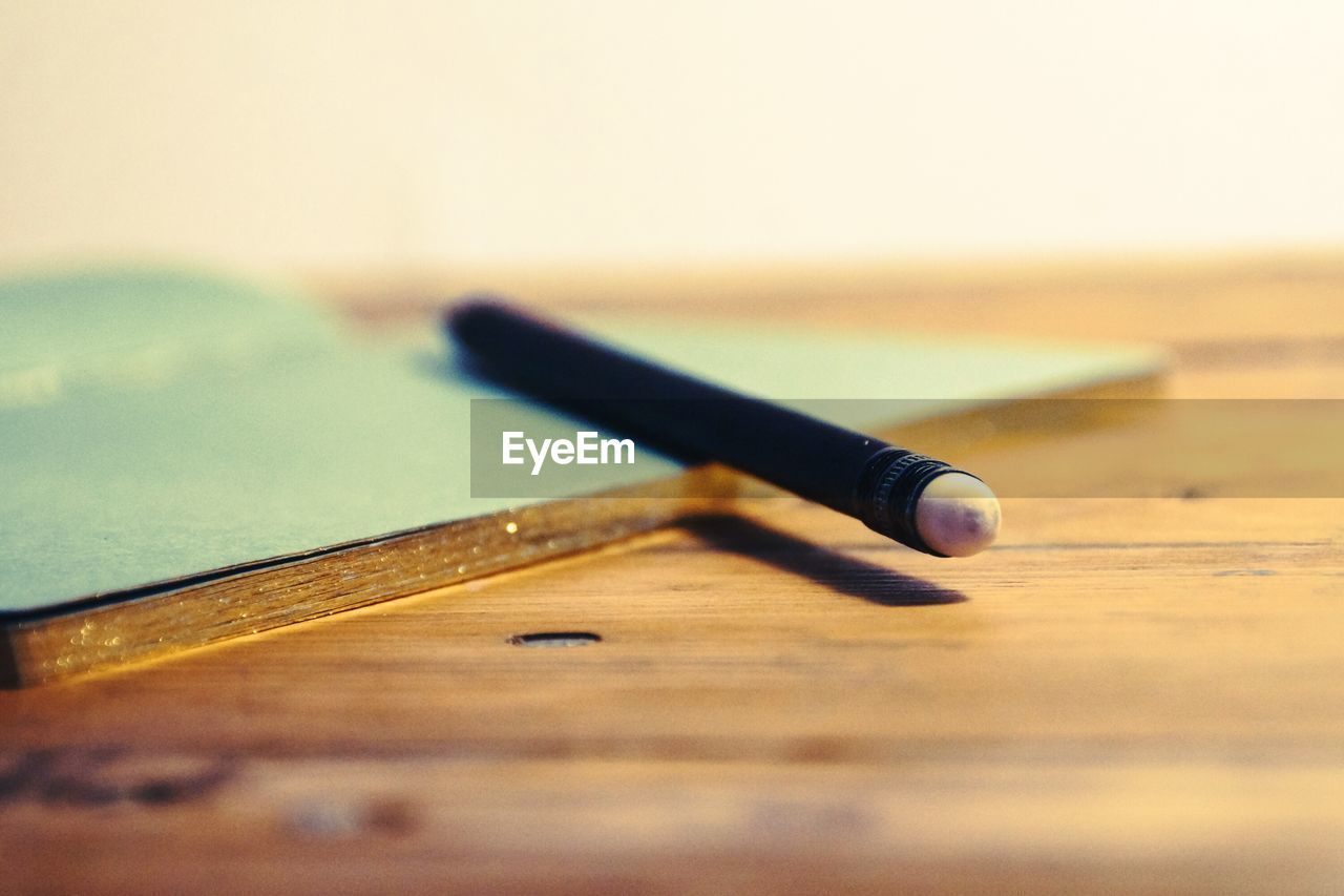 Close-up of pencil with book on wooden table