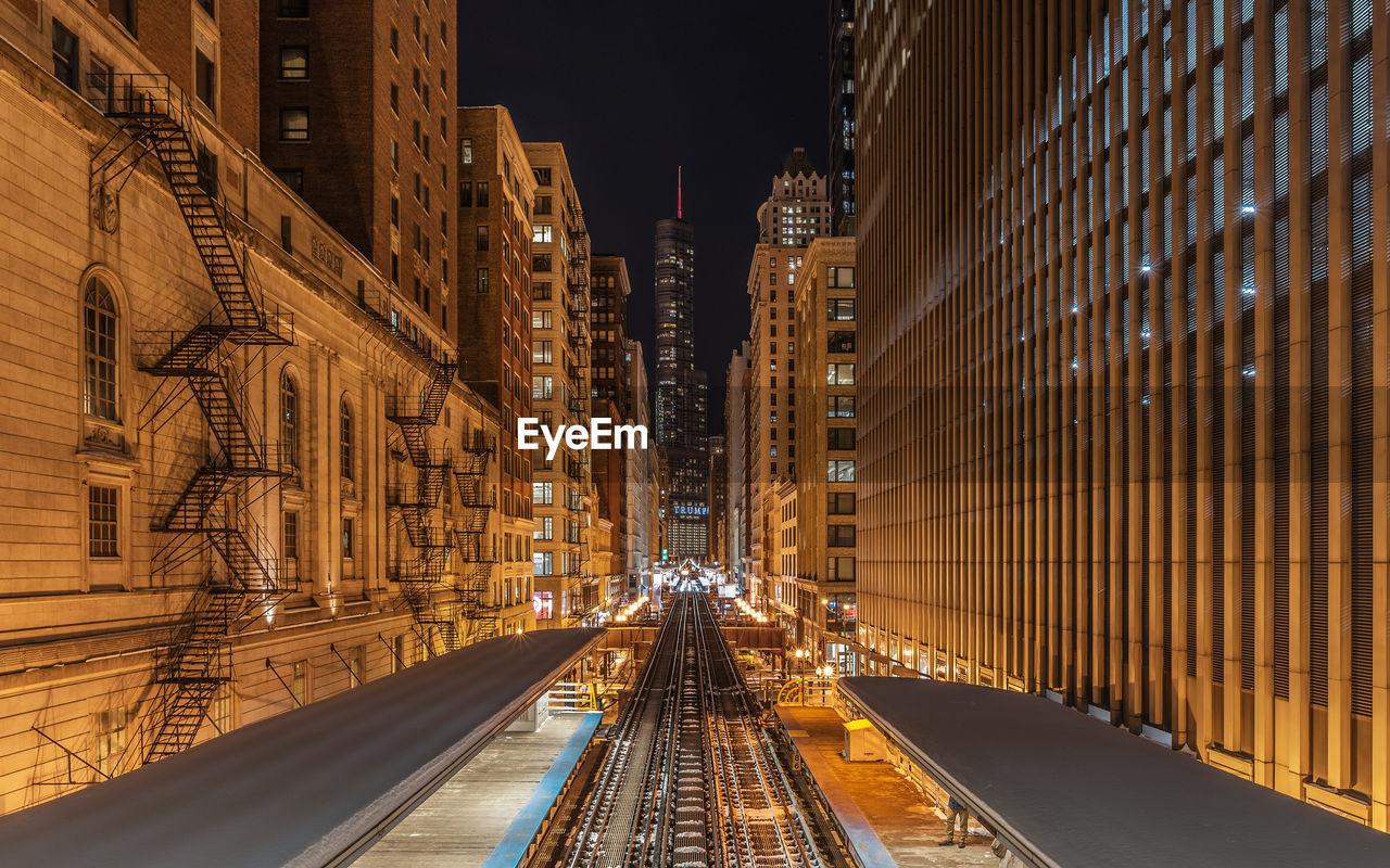 High Angle View Of Railroad Station Platform Amidst Illuminated City At Night