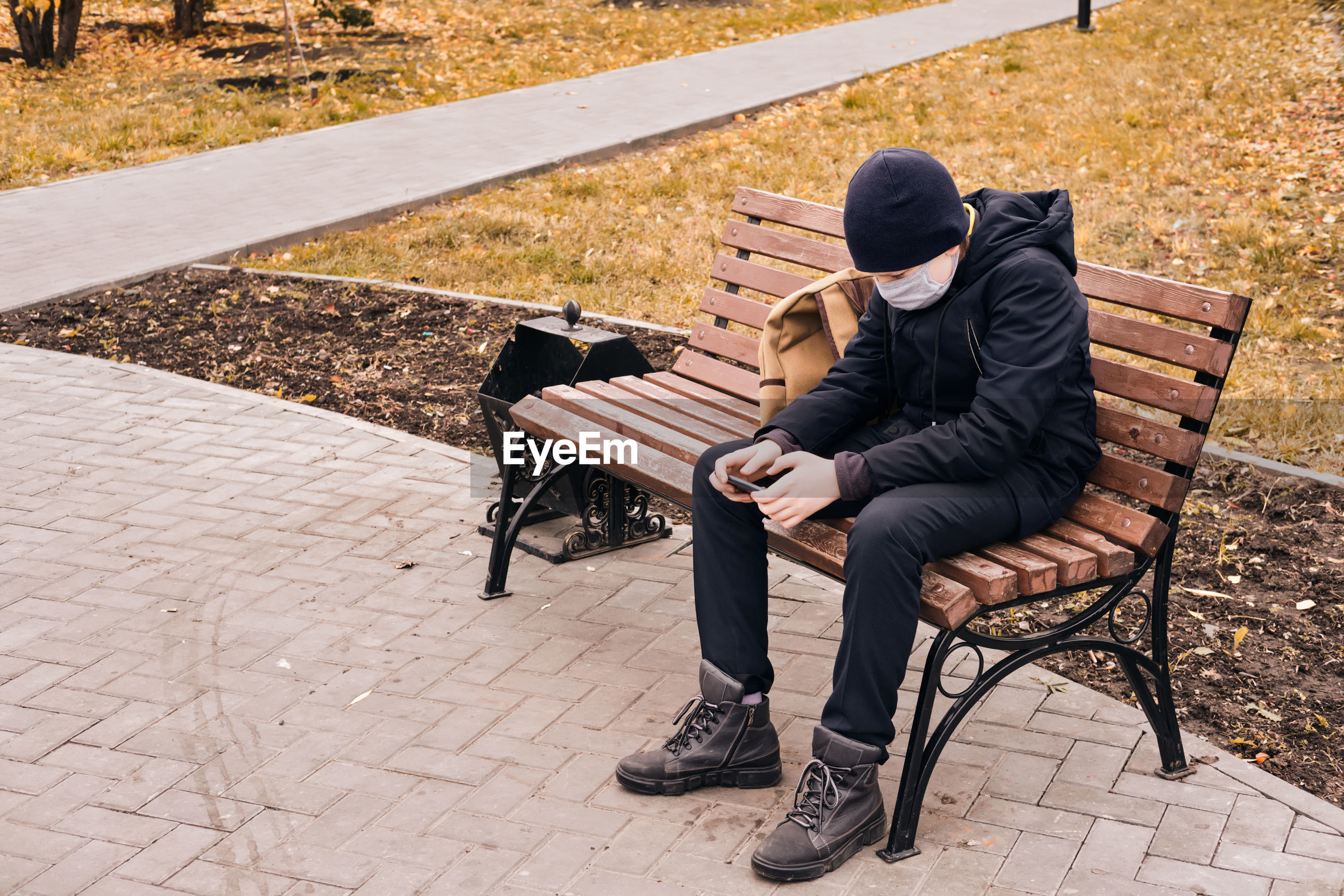 Boy wearing mask using phone sitting on bench at park