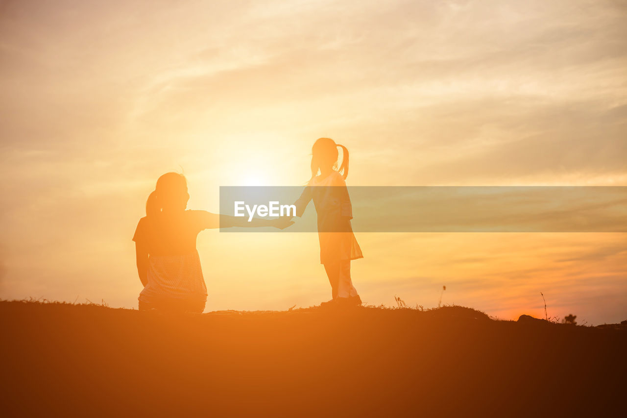 sunset, sky, orange color, togetherness, two people, real people, women, standing, lifestyles, leisure activity, bonding, cloud - sky, silhouette, beauty in nature, adult, love, side view, nature, land, sunlight, outdoors, positive emotion, couple - relationship