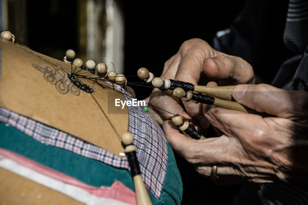 human hand, hand, real people, one person, human body part, playing, holding, musical instrument, men, music, skill, occupation, midsection, indoors, art and craft, artist, creativity, close-up, selective focus, finger, human limb