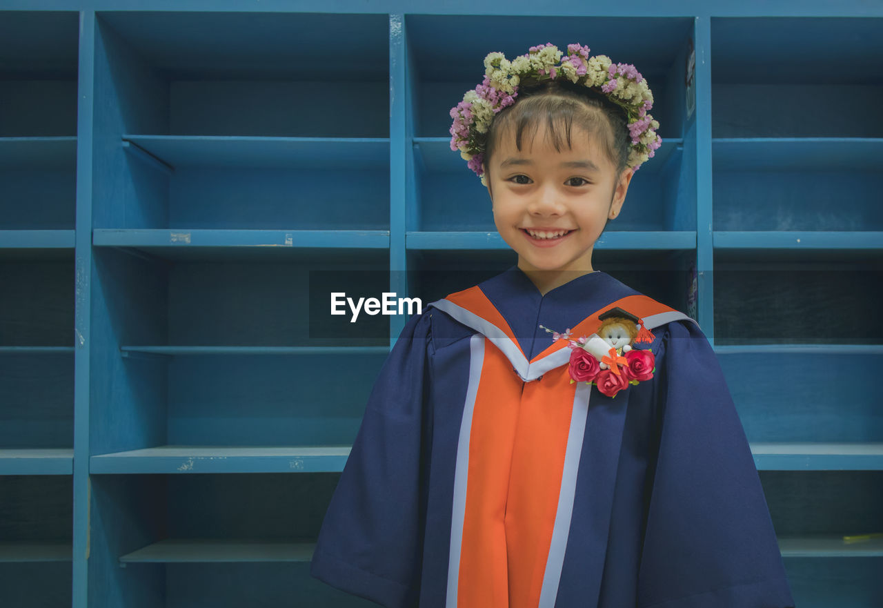 Portrait of smiling girl wearing flowers while standing against shelves