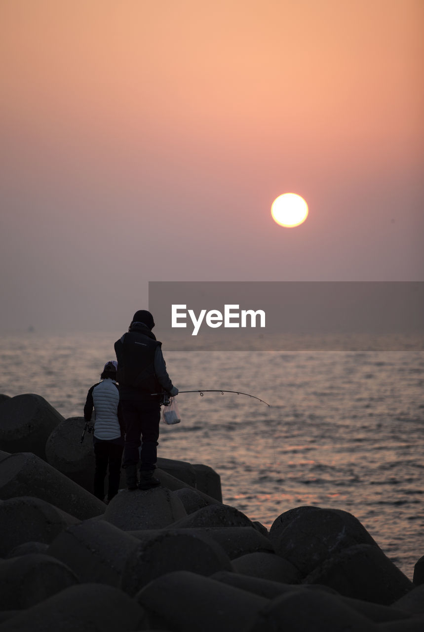 sunset, sun, sea, beauty in nature, nature, orange color, scenics, two people, real people, tranquility, tranquil scene, leisure activity, idyllic, beach, water, horizon over water, outdoors, rock - object, sky, silhouette, vacations, togetherness, sunlight, lifestyles, relaxation, full length, sitting, day, people