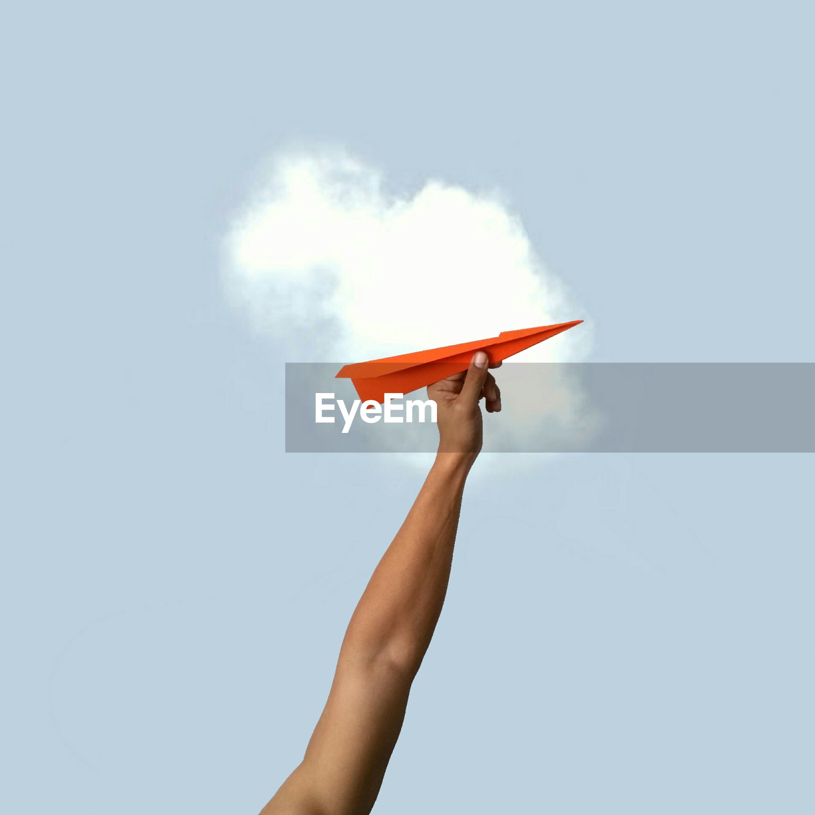 Low angle view of cropped hand holding orange paper rocket against sky