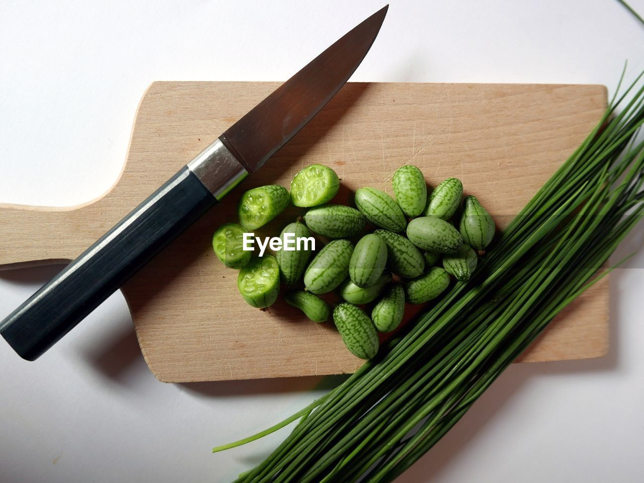 High angle view of cucumbers and spring onions with kitchen knife on cutting board