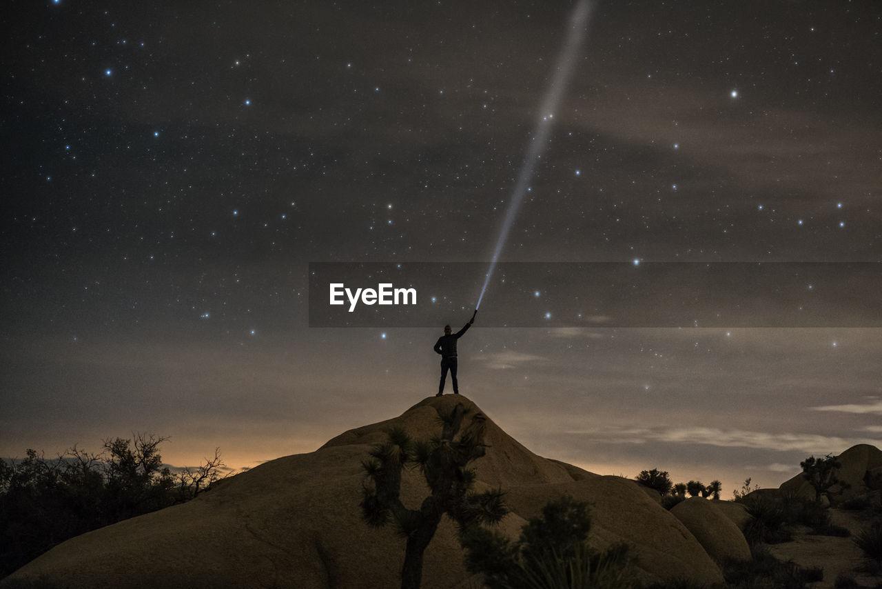 Man Holding Flashlight At Night