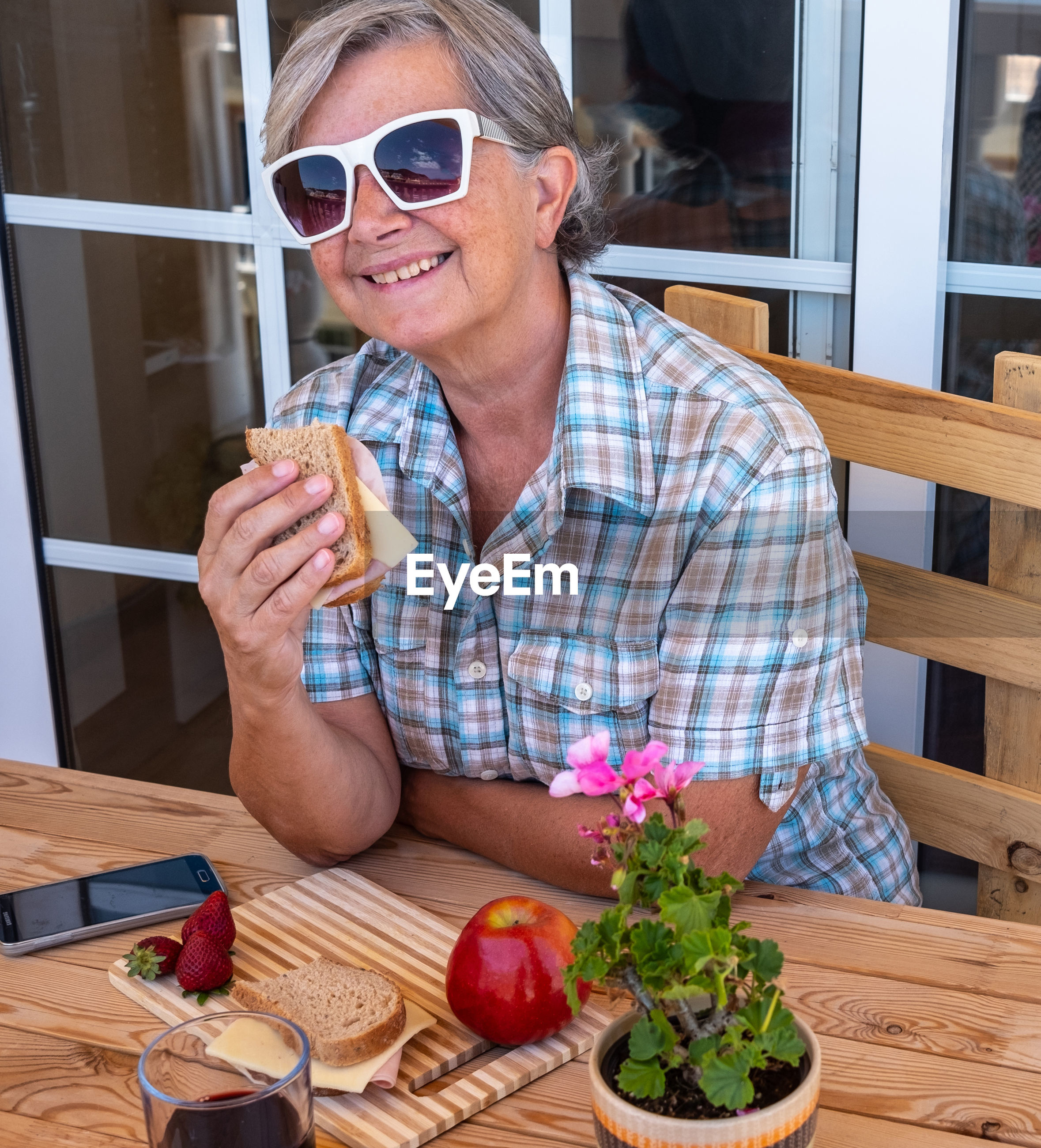 Portrait of woman in sunglasses having breakfast at cafe