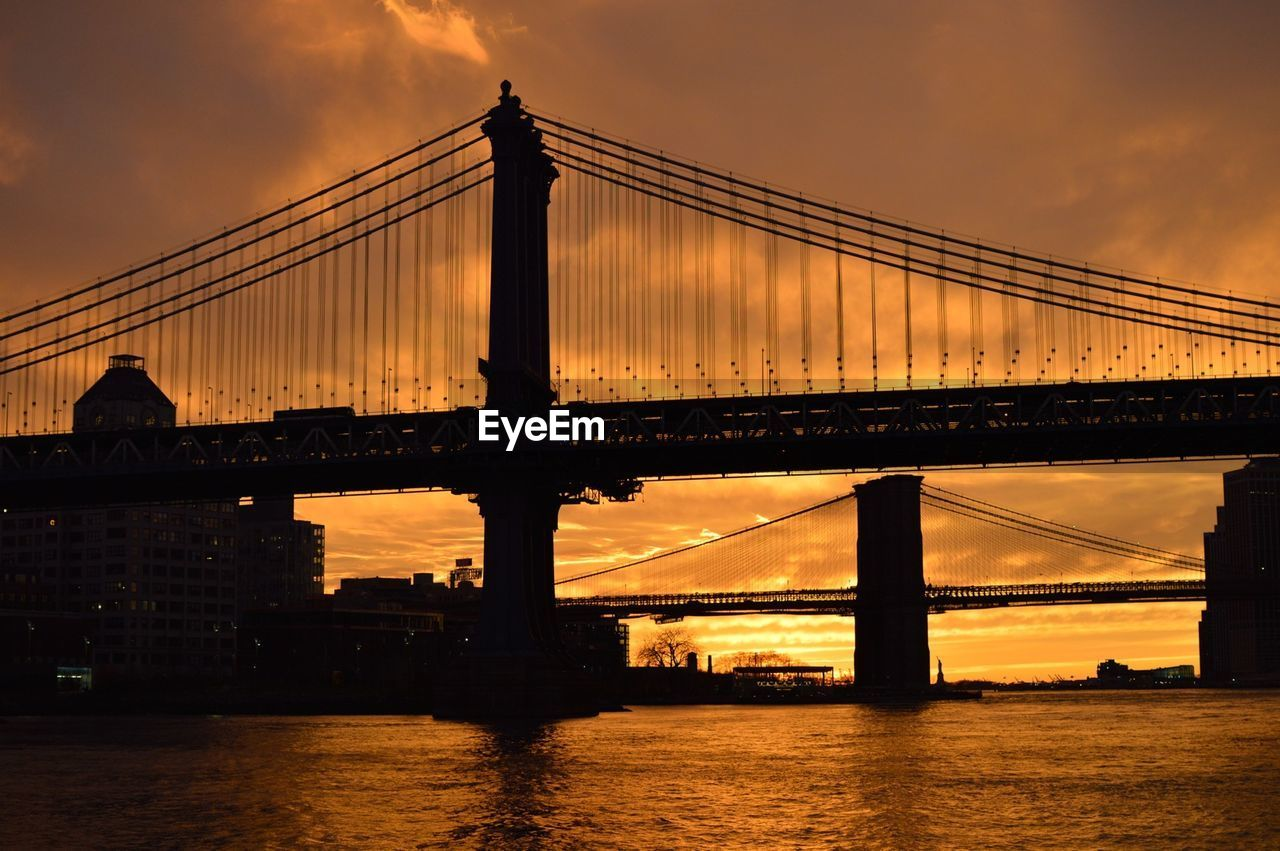 Low angle view of silhouette brooklyn bridge over river against orange sky