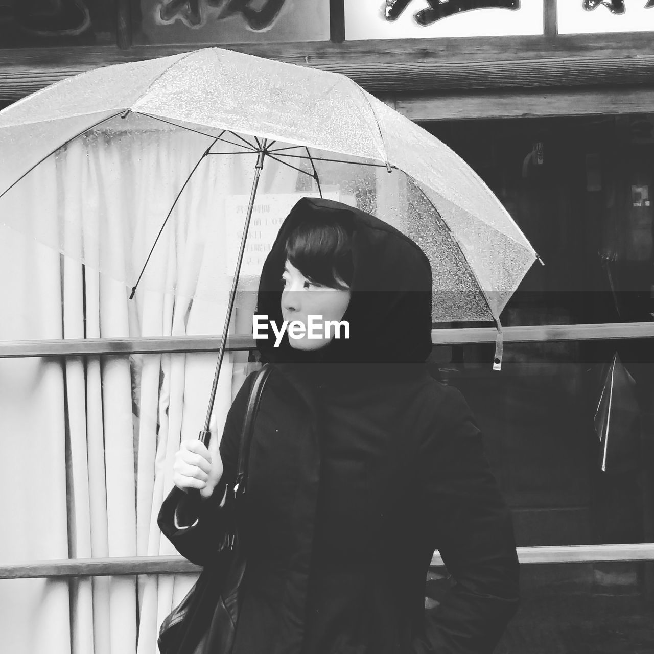 Woman With Umbrella In City During Monsoon