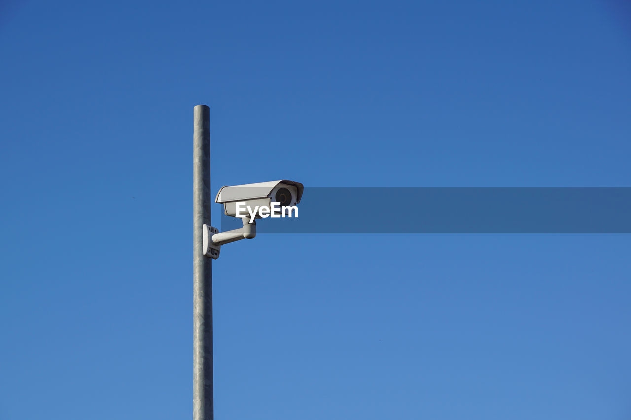 security camera, blue, copy space, clear sky, sky, technology, security system, surveillance, pole, security, safety, no people, day, protection, low angle view, control, outdoors, nature, white color, metal, electrical equipment, big brother - orwellian concept