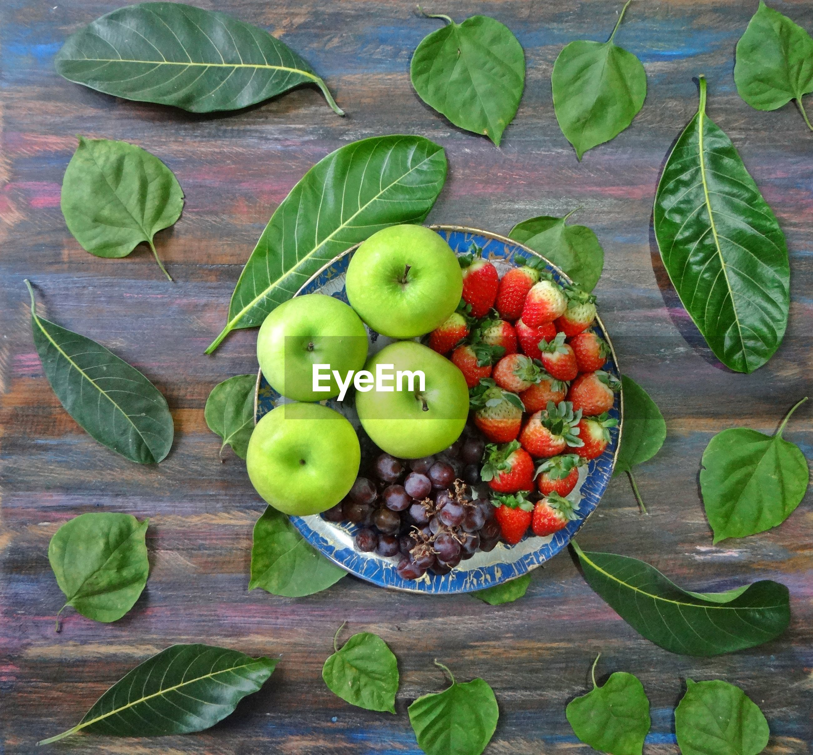 High angle view of fruits in plate with leaves on wooden table