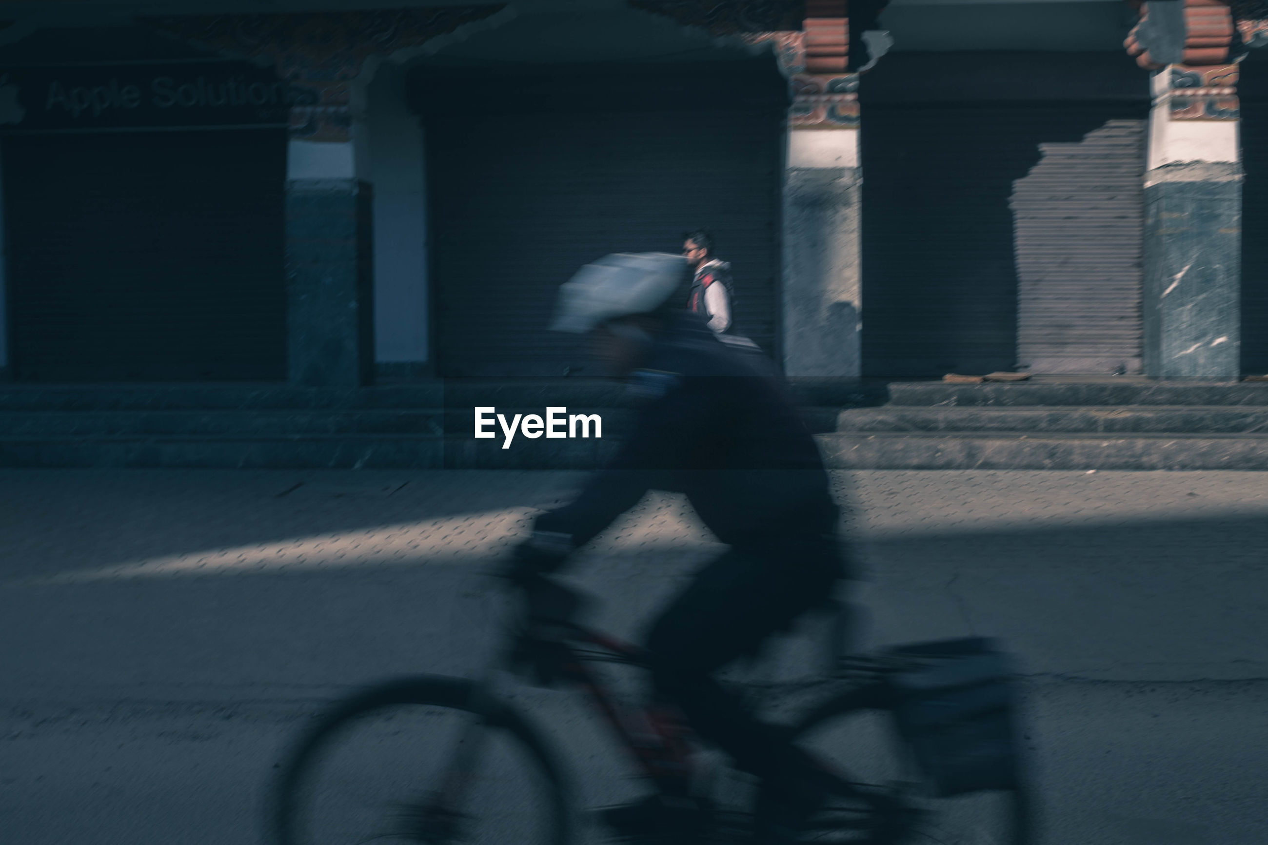 Blurred motion of man riding bicycle on street