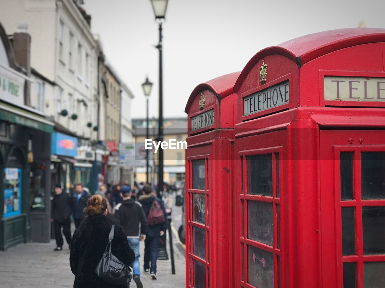telephone booth, communication, red, pay phone, street, connection, built structure, architecture, building exterior, outdoors, city, telephone, day, real people, men, telecommunications equipment, technology, sky, people