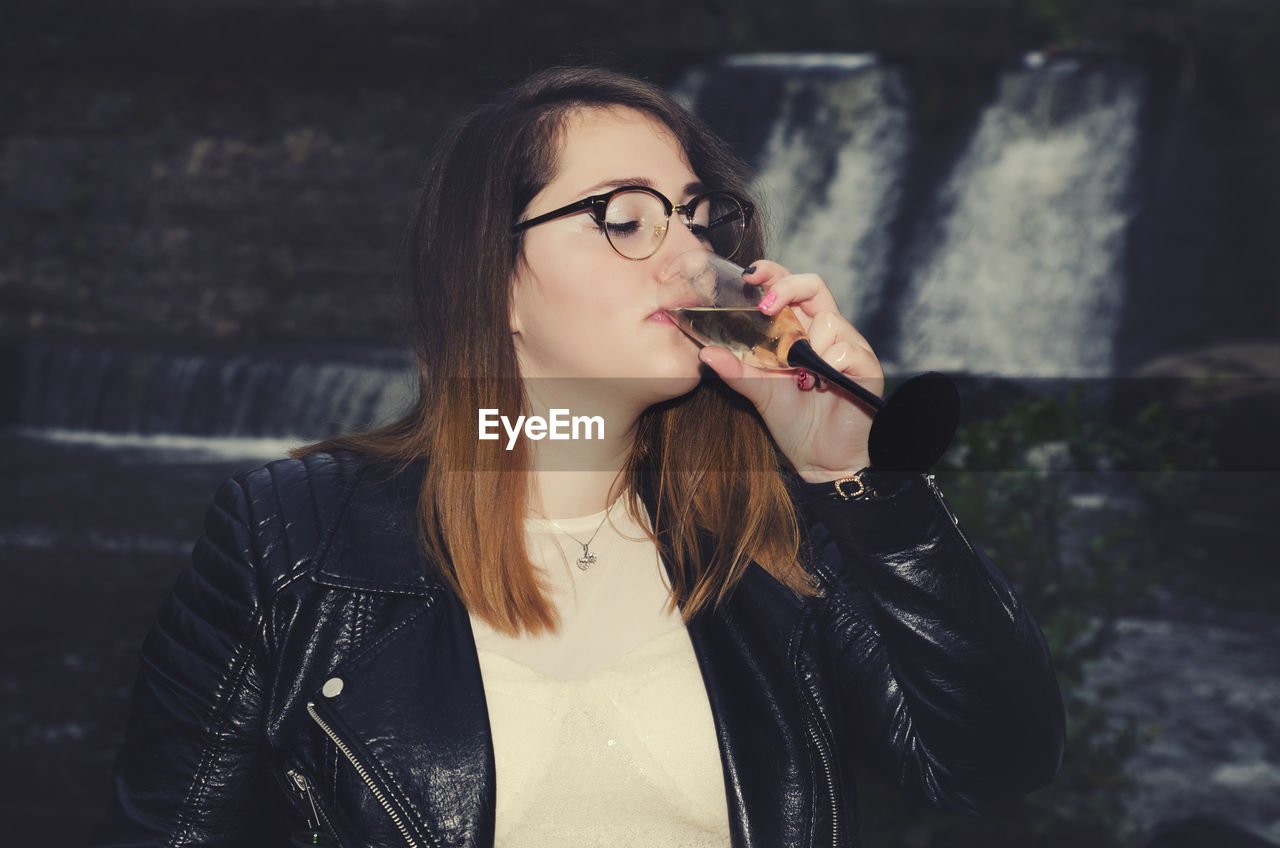 Young Woman Drinking Champagne Against Waterfall