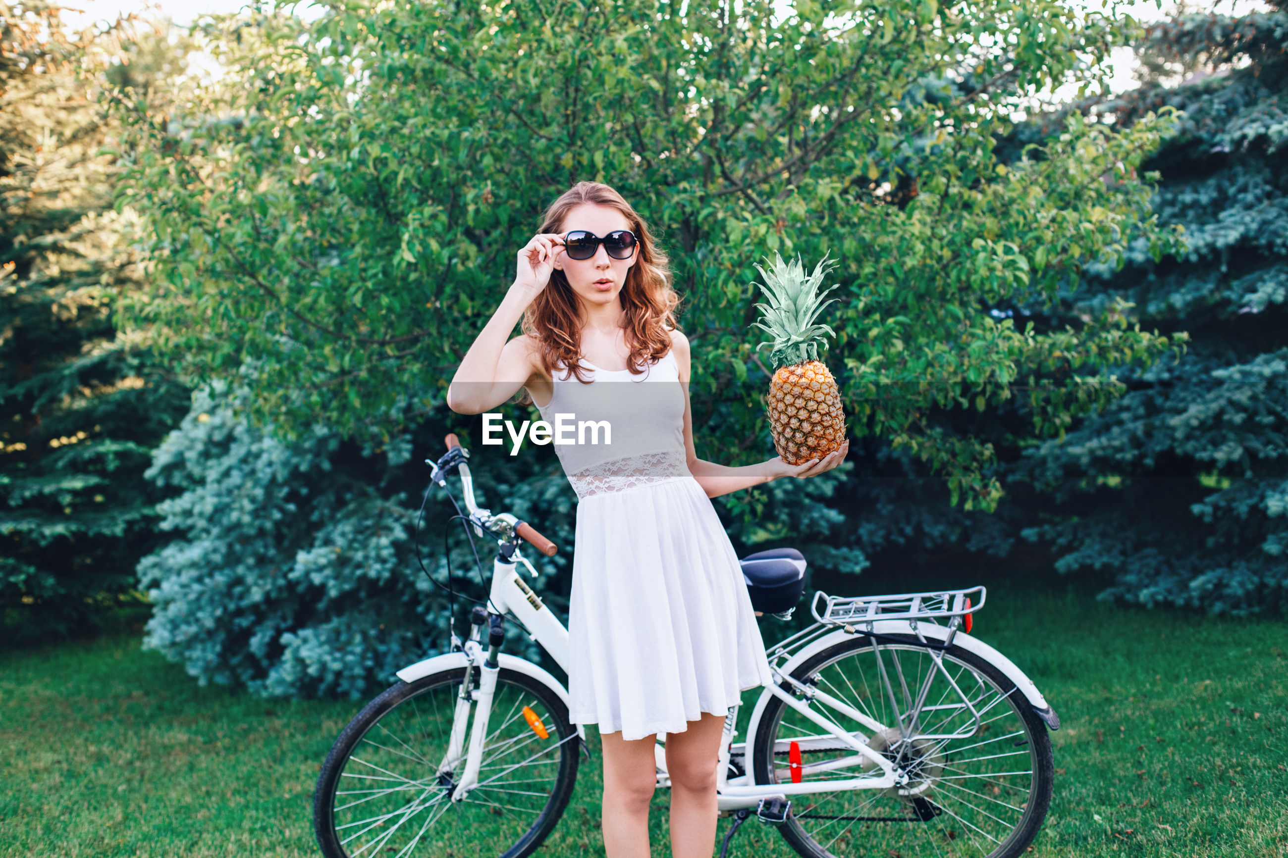 Portrait of young woman holding pineapple while standing on grass by bicycle against trees