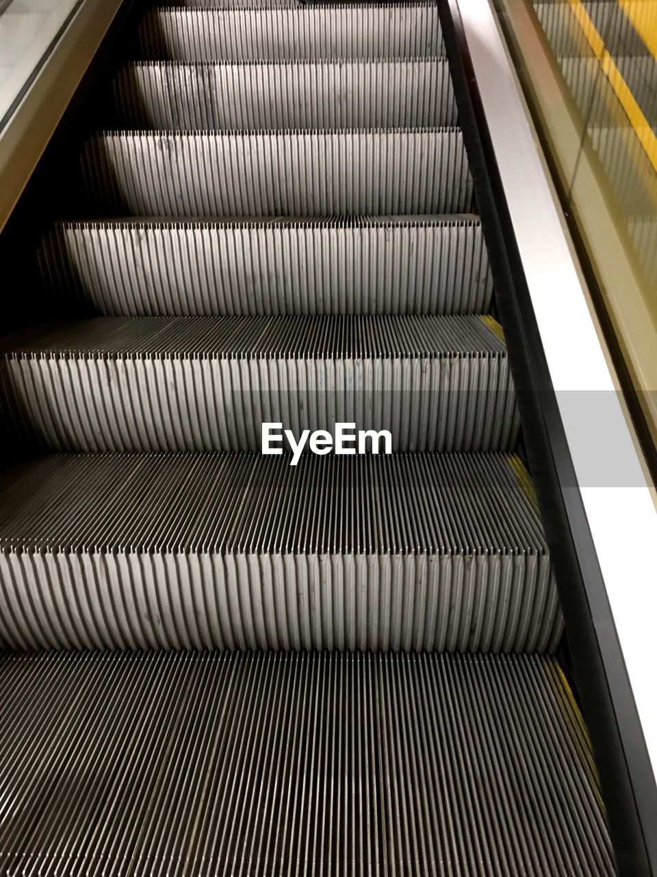 escalator, indoors, architecture, pattern, convenience, transportation, the way forward, steps and staircases, railing, staircase, direction, no people, high angle view, technology, modern, built structure, empty, connection, illuminated, moving walkway, ceiling, silver colored