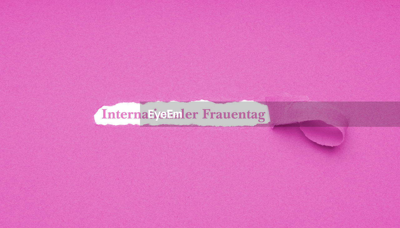 Close-up of text seen through torn pink paper