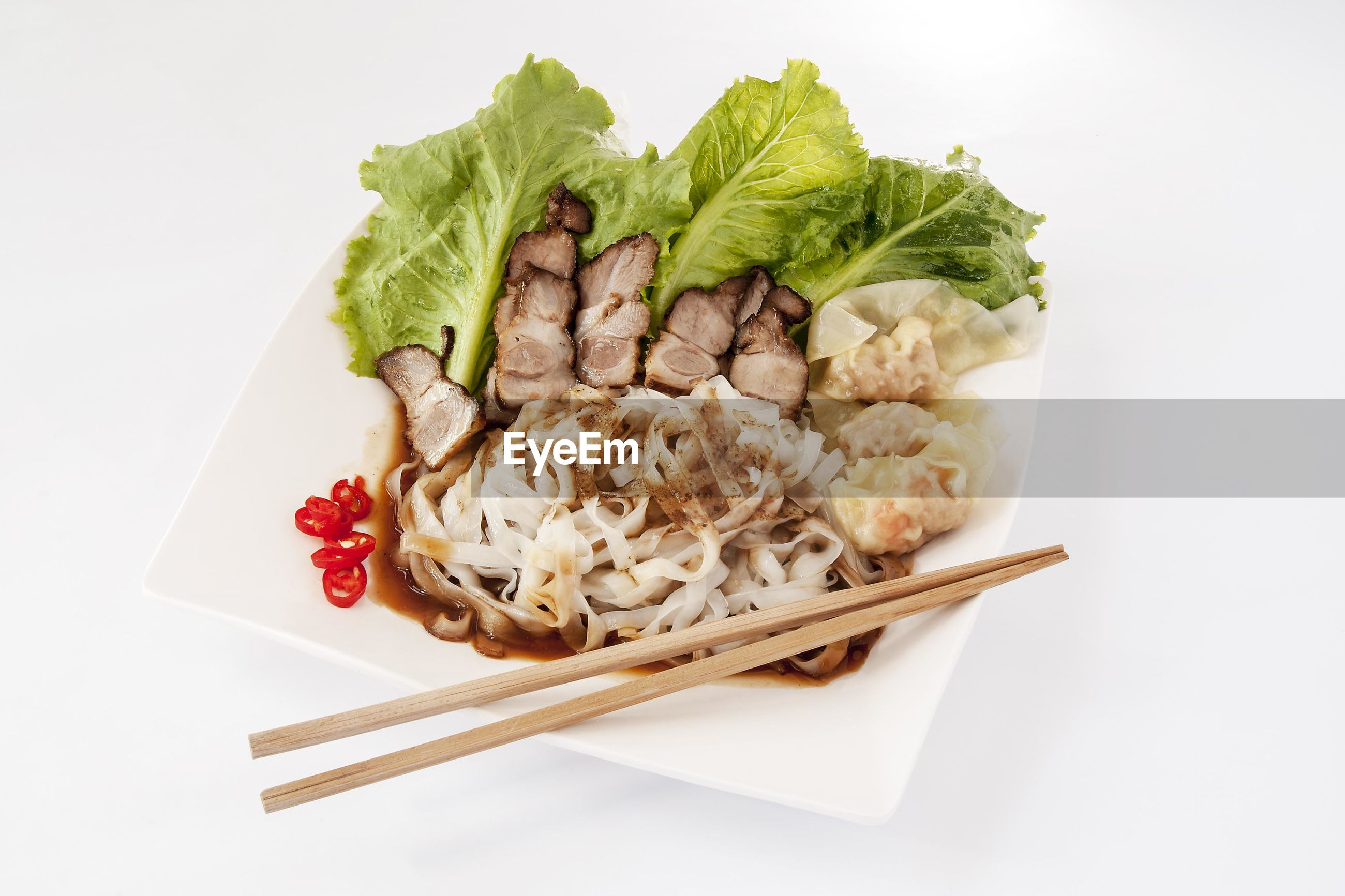 High angle view of meat and dumplings with chopsticks in plate over white background