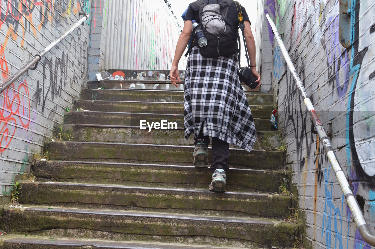 steps, steps and staircases, staircase, graffiti, one person, city, city life, built structure, people, outdoors, building exterior, climbing, real people, adult, day, architecture, young adult, adults only, one young woman only