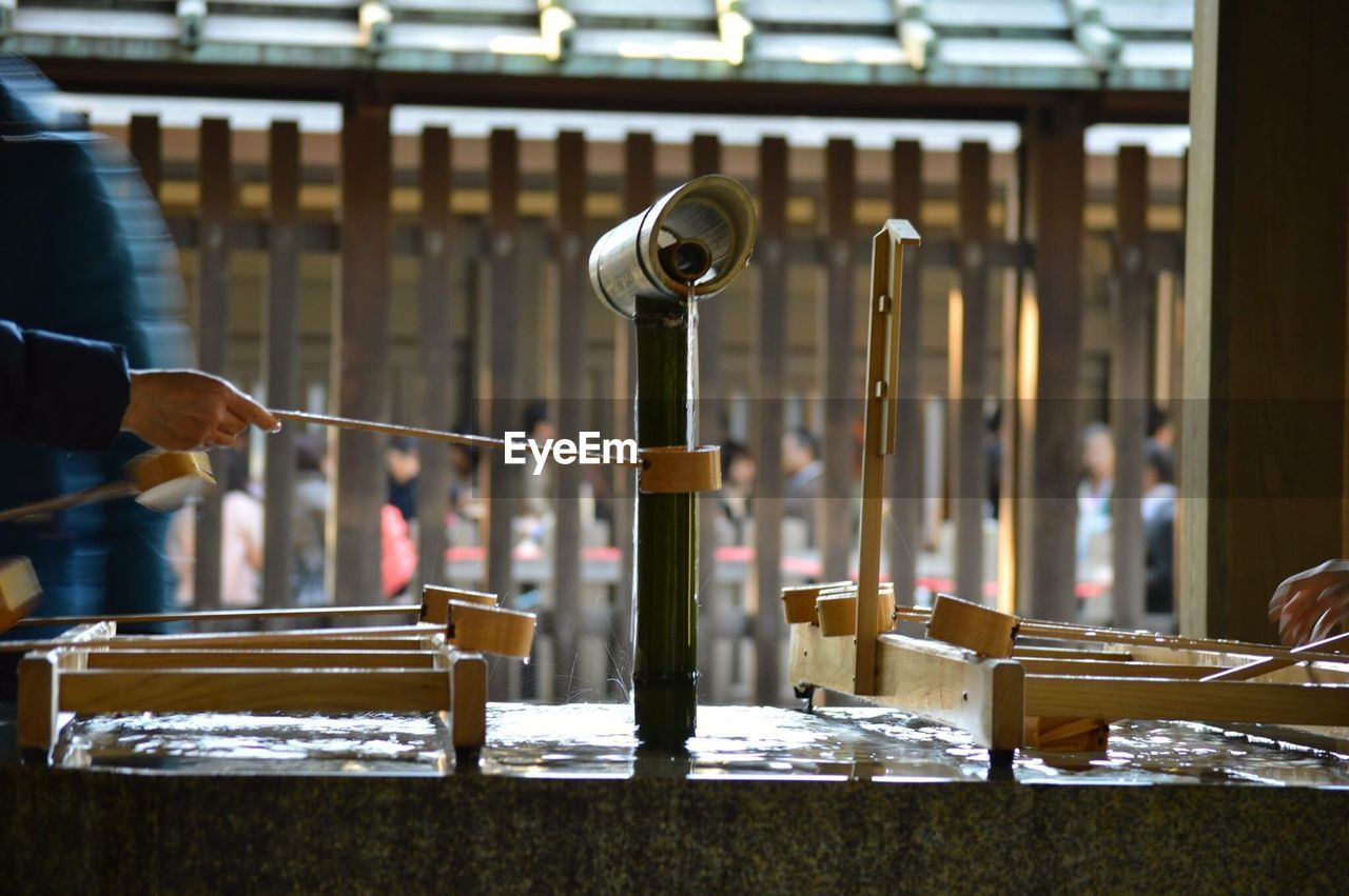 Cropped hand filling water in bamboo dipper at shrine