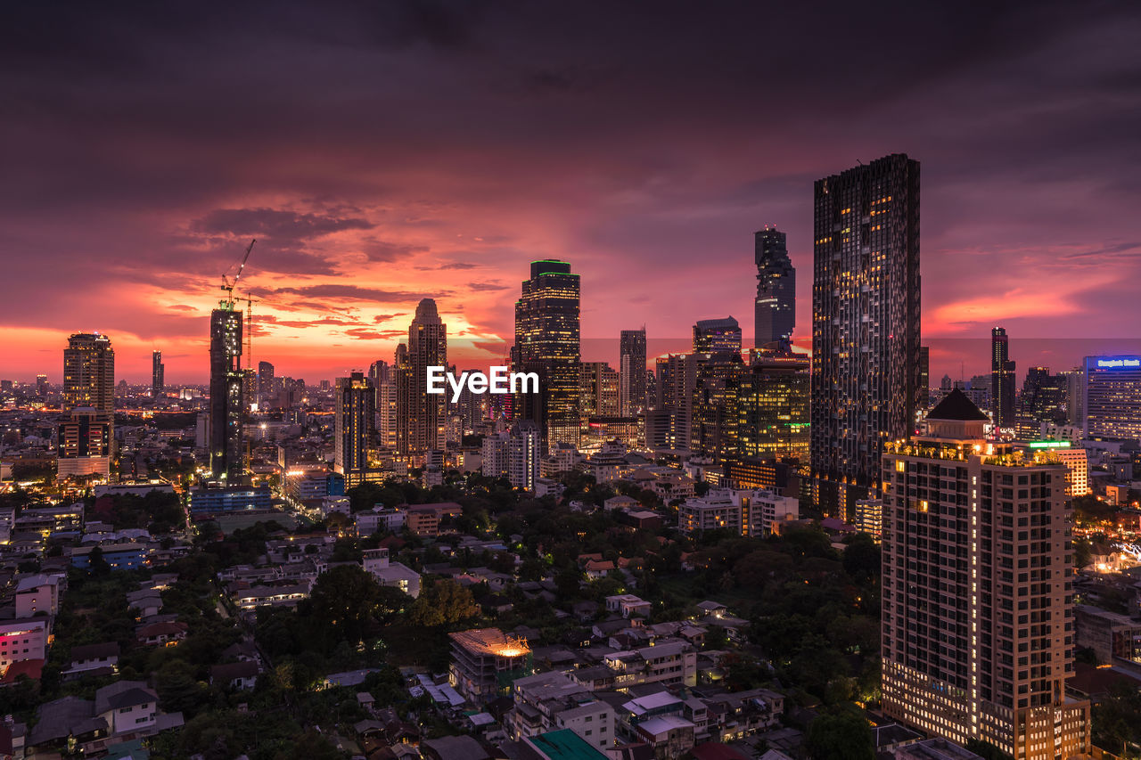Illuminated Buildings In City Against Cloudy Orange Sky At Dusk