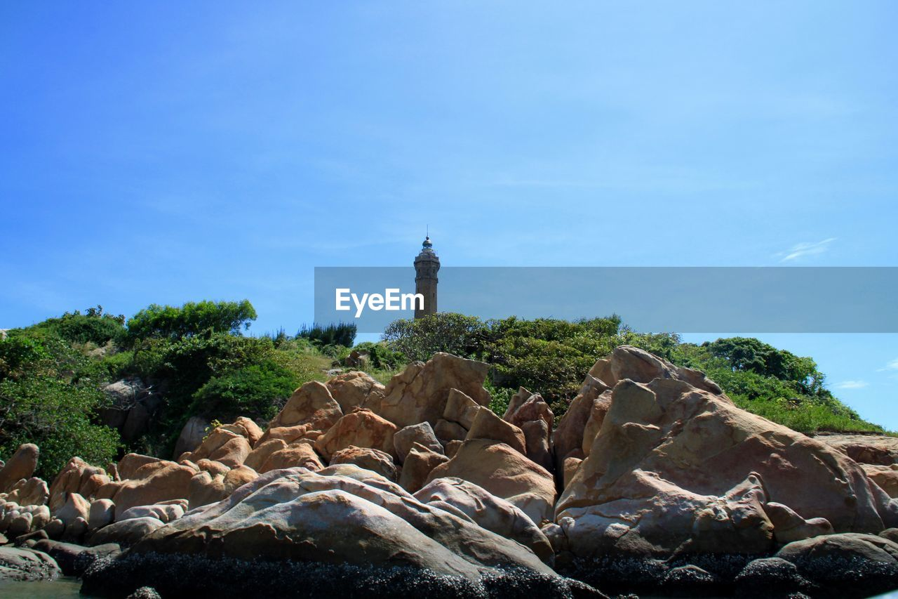 nature, sky, rock - object, beauty in nature, day, outdoors, mammal, no people, lighthouse, water, animal themes, tree