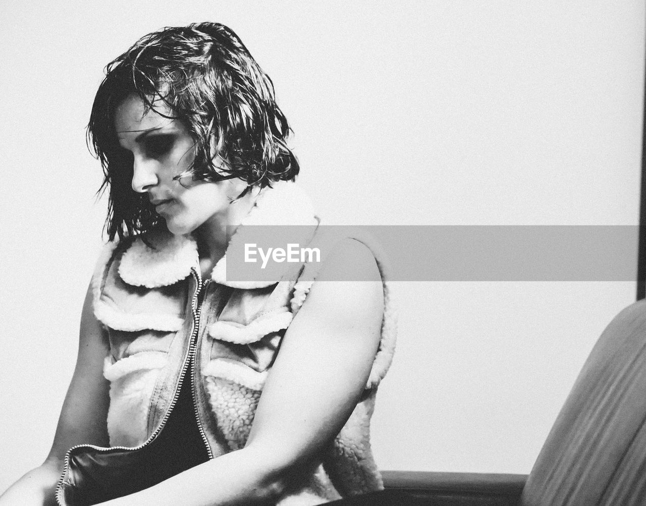 Woman looking down while sitting on chair against wall