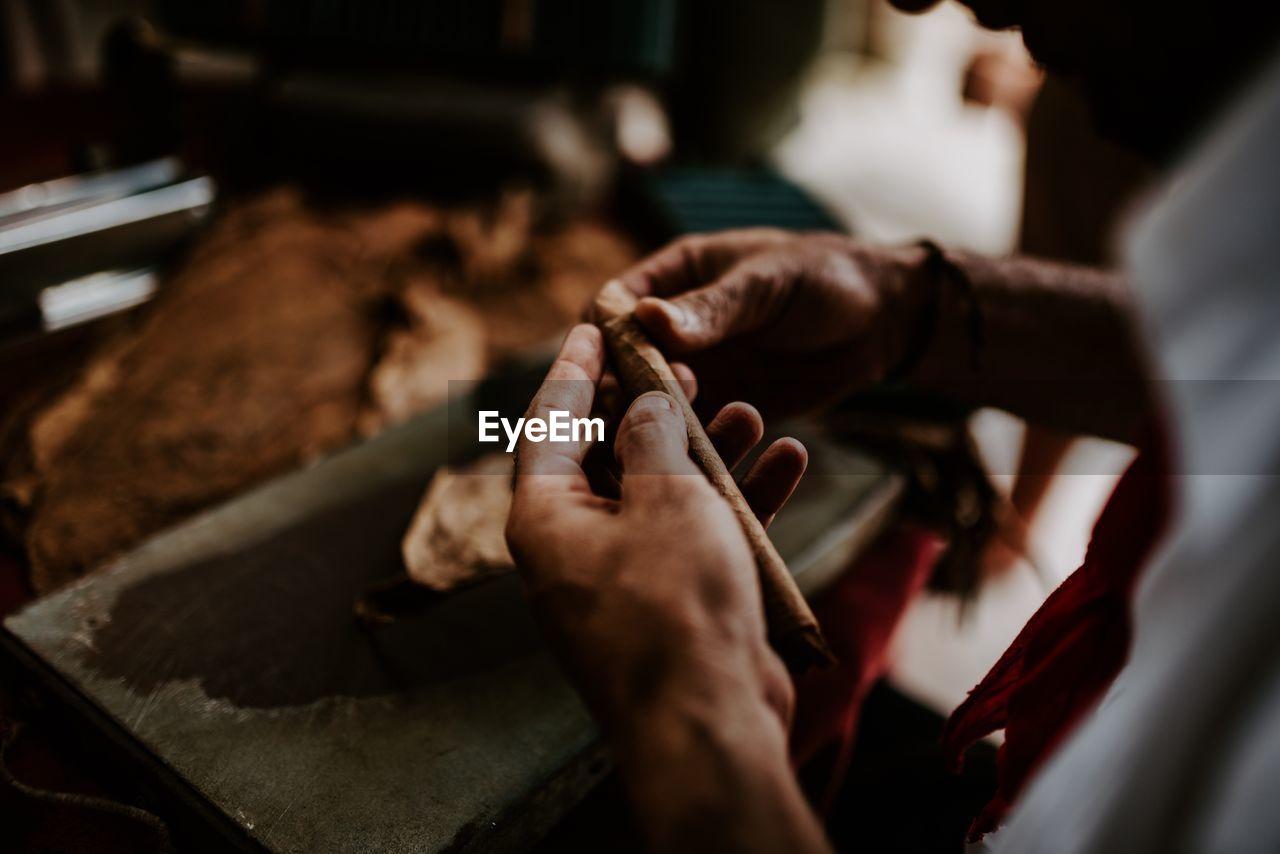 Cropped Hands Of Craftsperson Making Cigar Leaves At Workshop