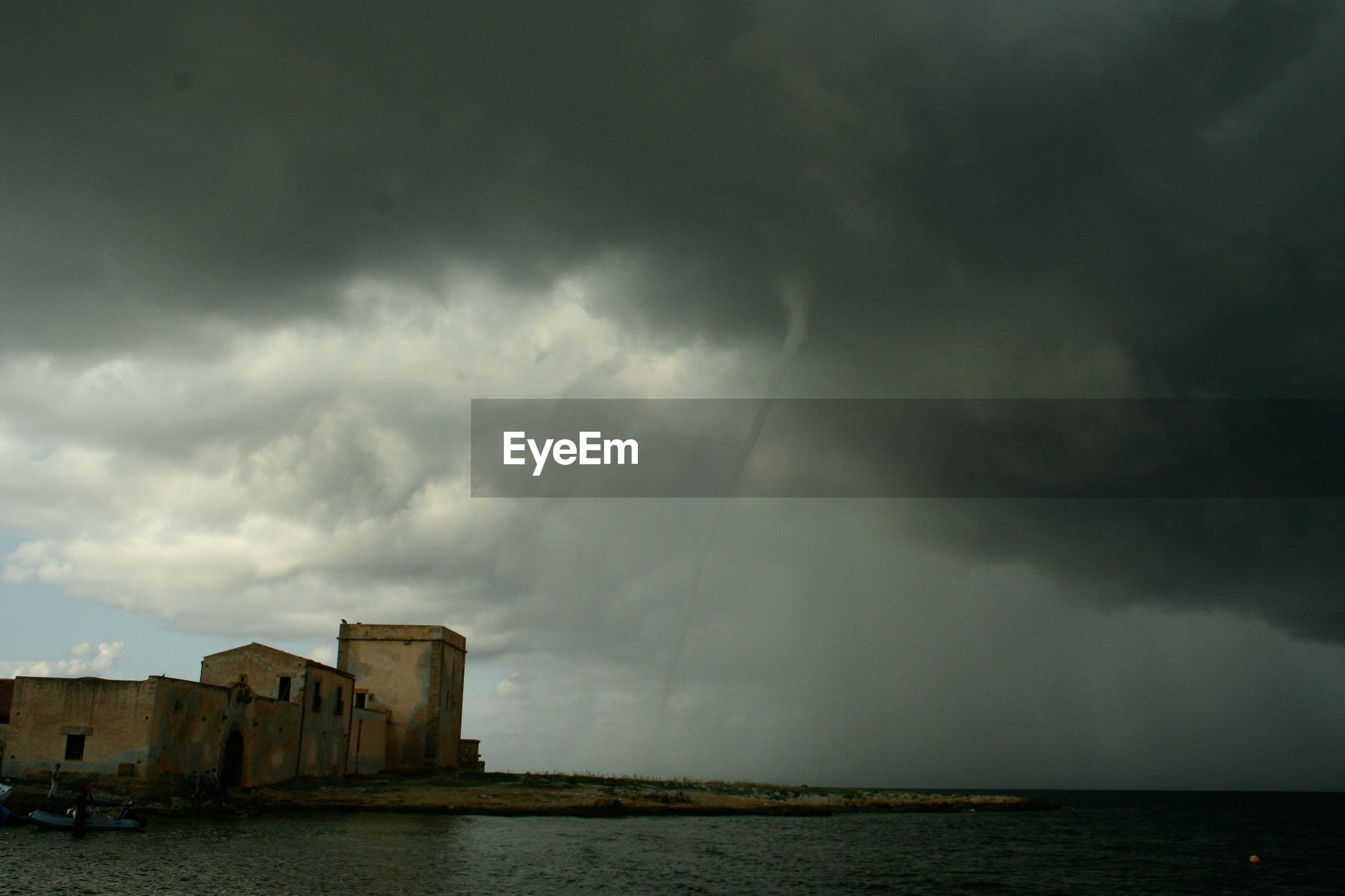 Low angle view of tornado at sea against cloudy sky