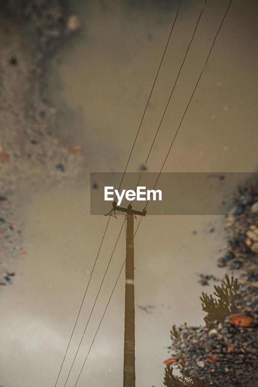 Reflection of electricity pylon on puddle