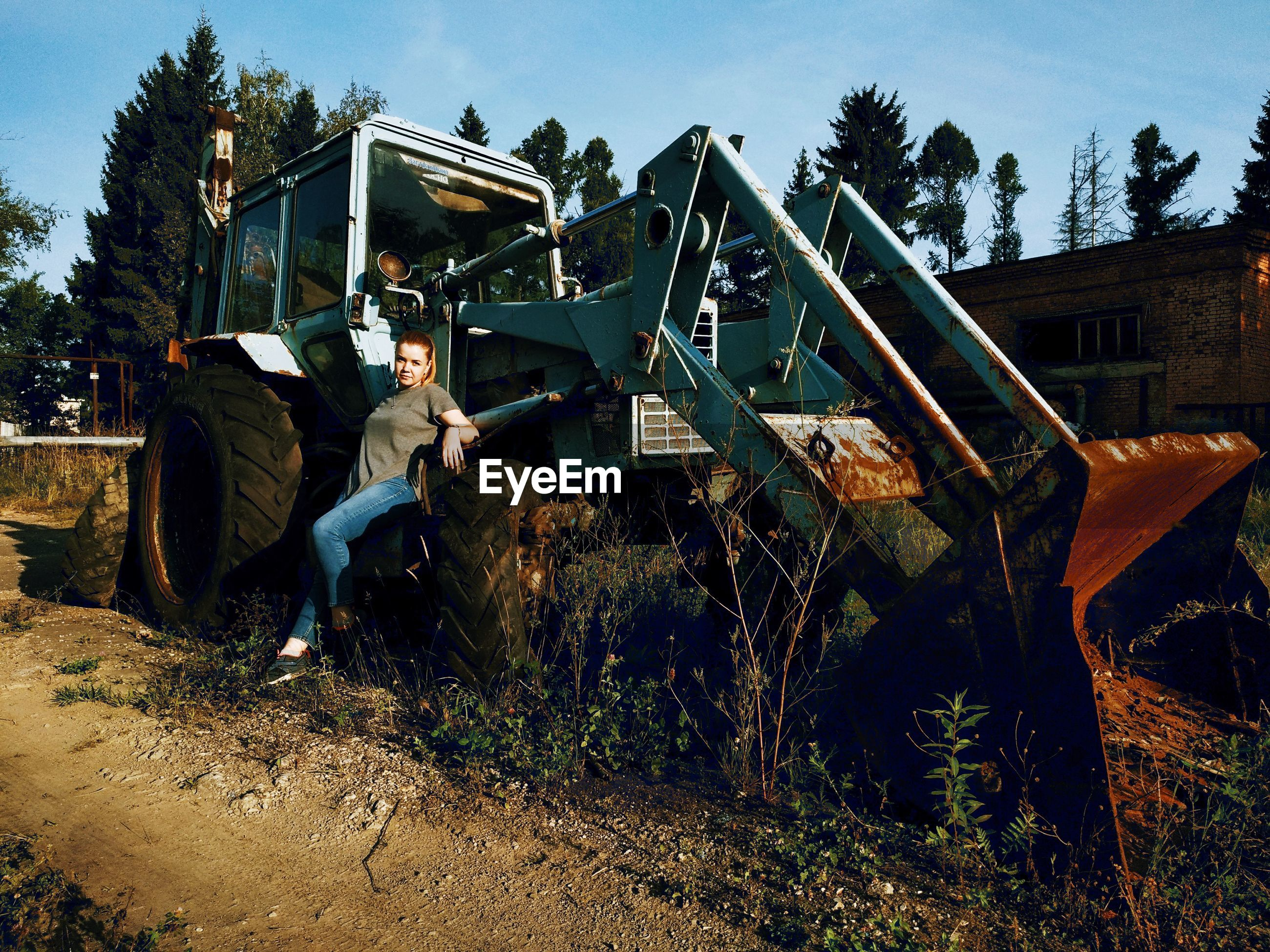 Portrait of woman standing by bulldozer
