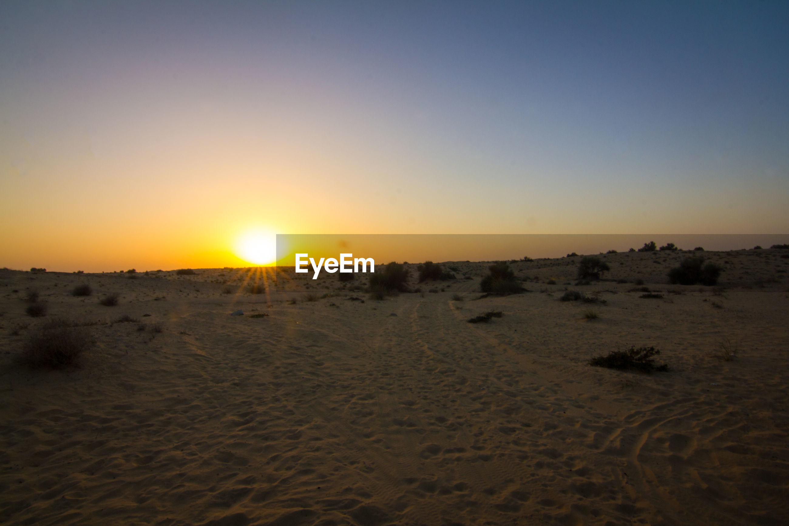 SCENIC VIEW OF DESERT AGAINST CLEAR SKY AT SUNSET