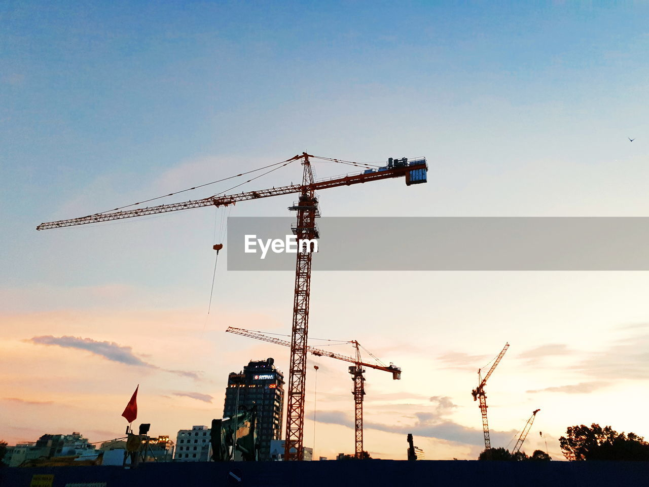 sky, crane - construction machinery, construction industry, construction site, machinery, industry, sunset, development, cloud - sky, nature, construction machinery, architecture, construction equipment, incomplete, no people, low angle view, crane, silhouette, built structure, outdoors, industrial equipment