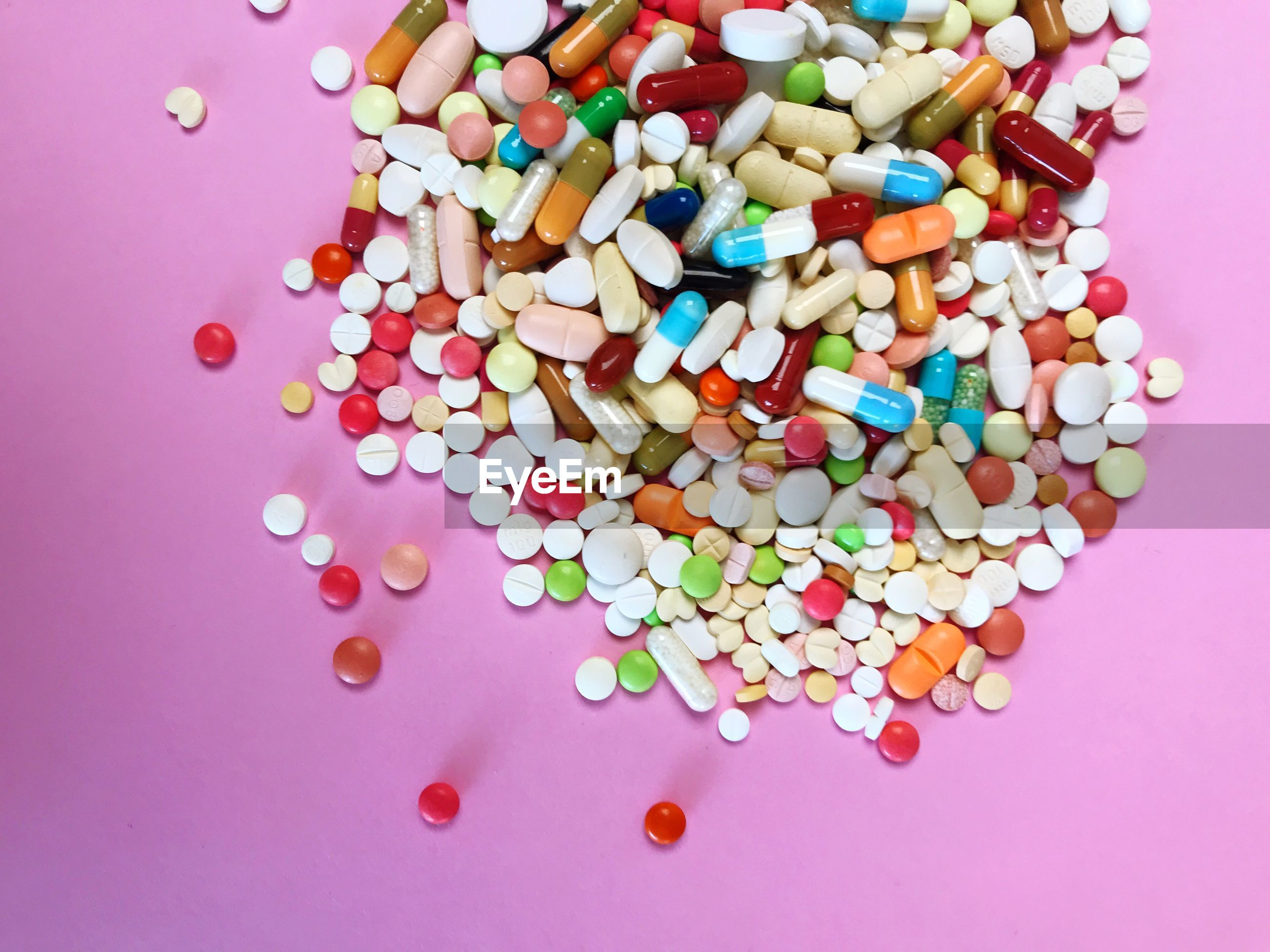 Directly above shot pills on pink background
