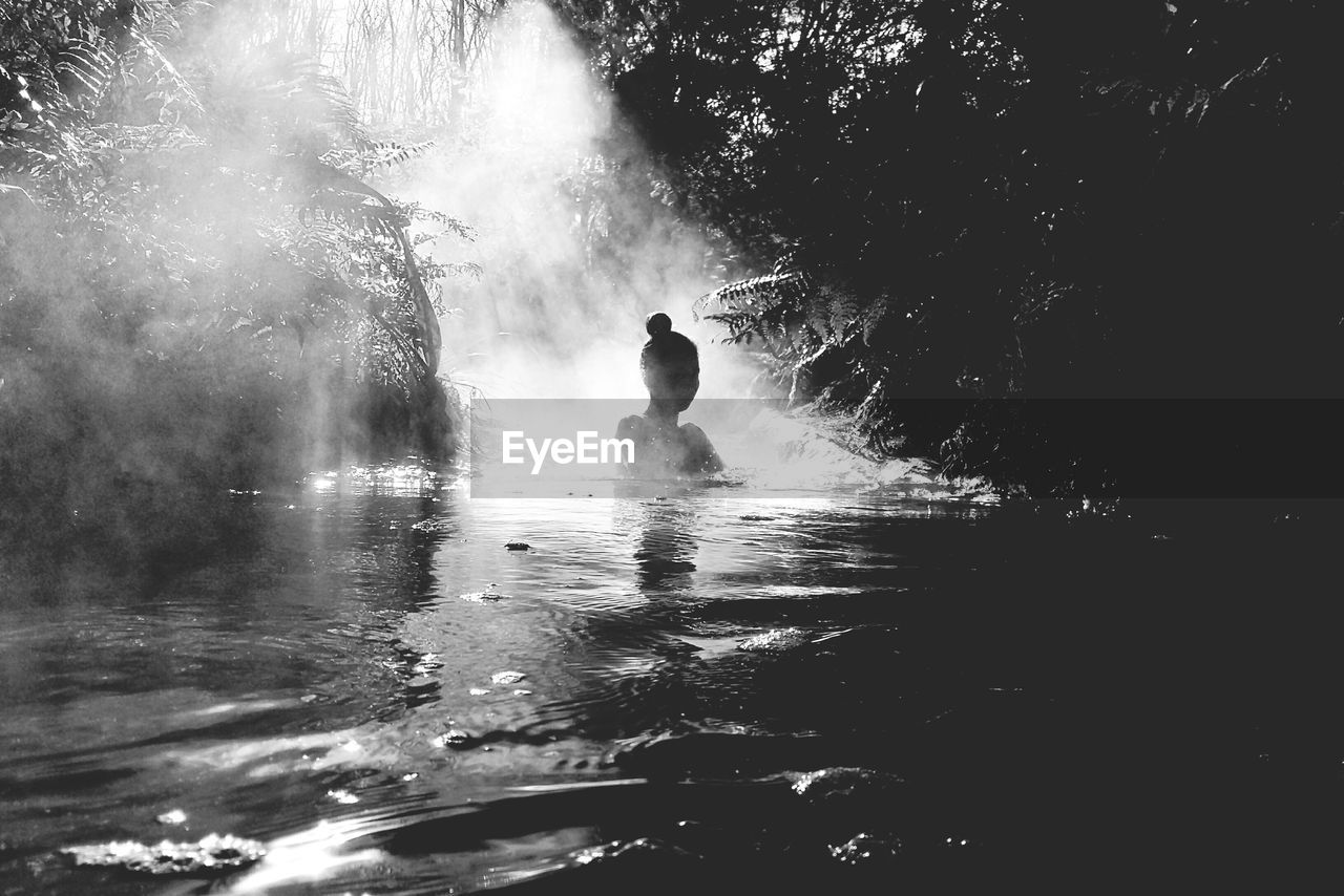 Silhouette Woman Swimming In Lake At Forest