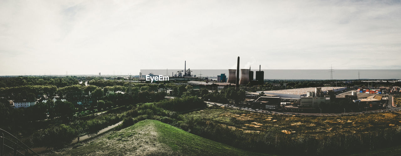 architecture, building exterior, sky, built structure, industry, nature, day, no people, plant, factory, city, outdoors, high angle view, building, transportation, water, road, copy space, cloud - sky, cityscape, industrial district, pollution