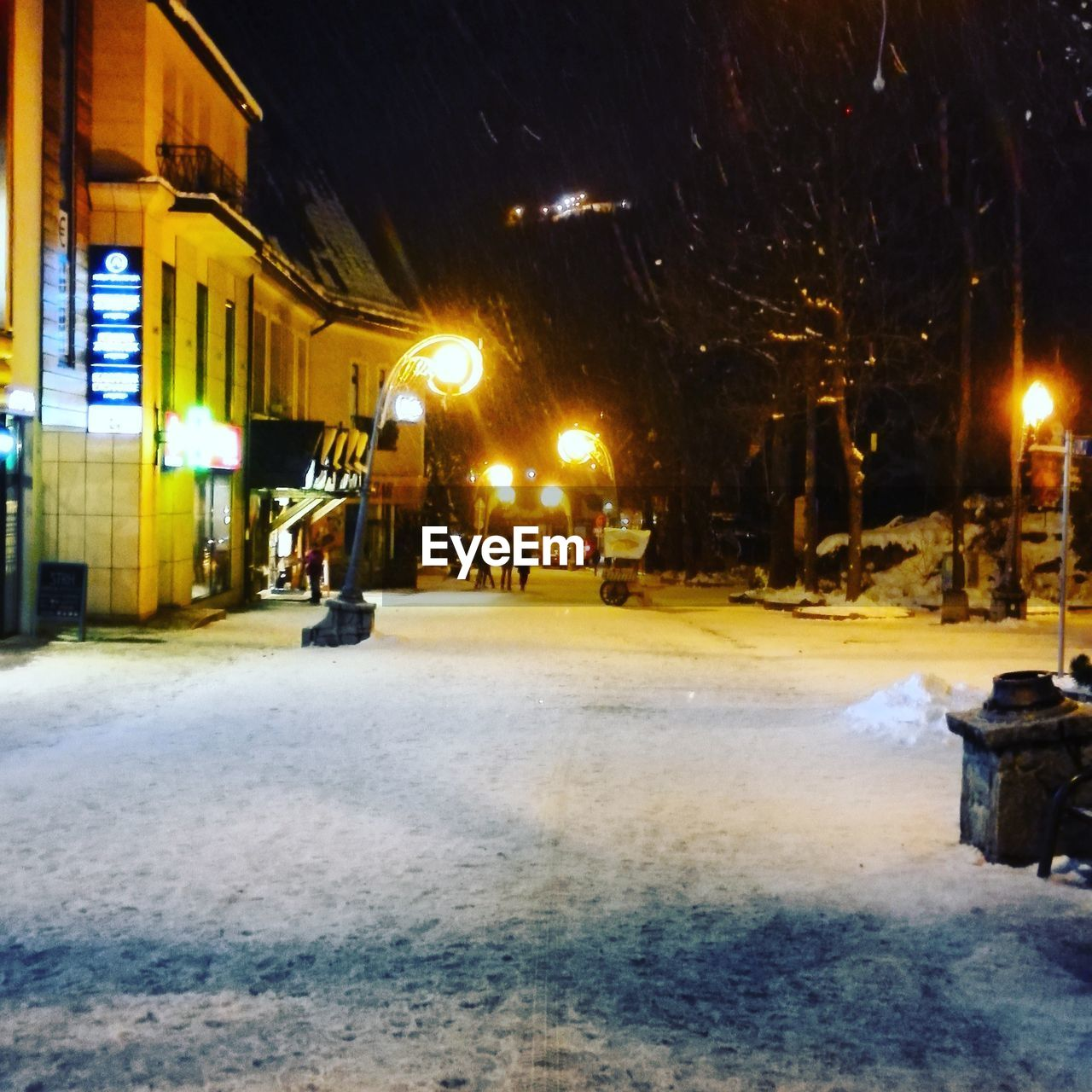 SNOW COVERED STREET IN CITY AT NIGHT