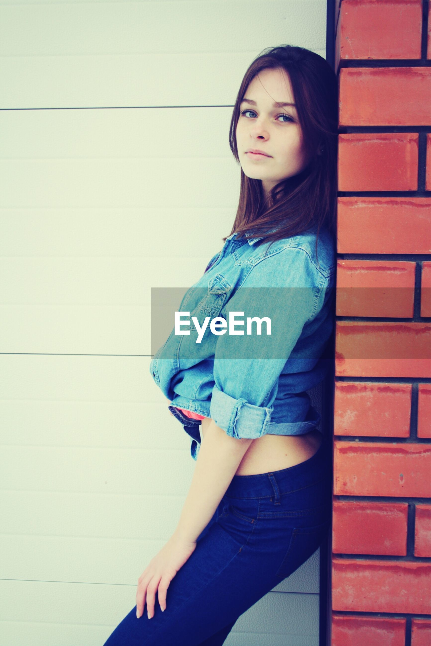 young adult, young women, front view, looking at camera, portrait, person, casual clothing, lifestyles, standing, wall - building feature, three quarter length, long hair, fashion, leisure activity, fashionable, smiling, black hair