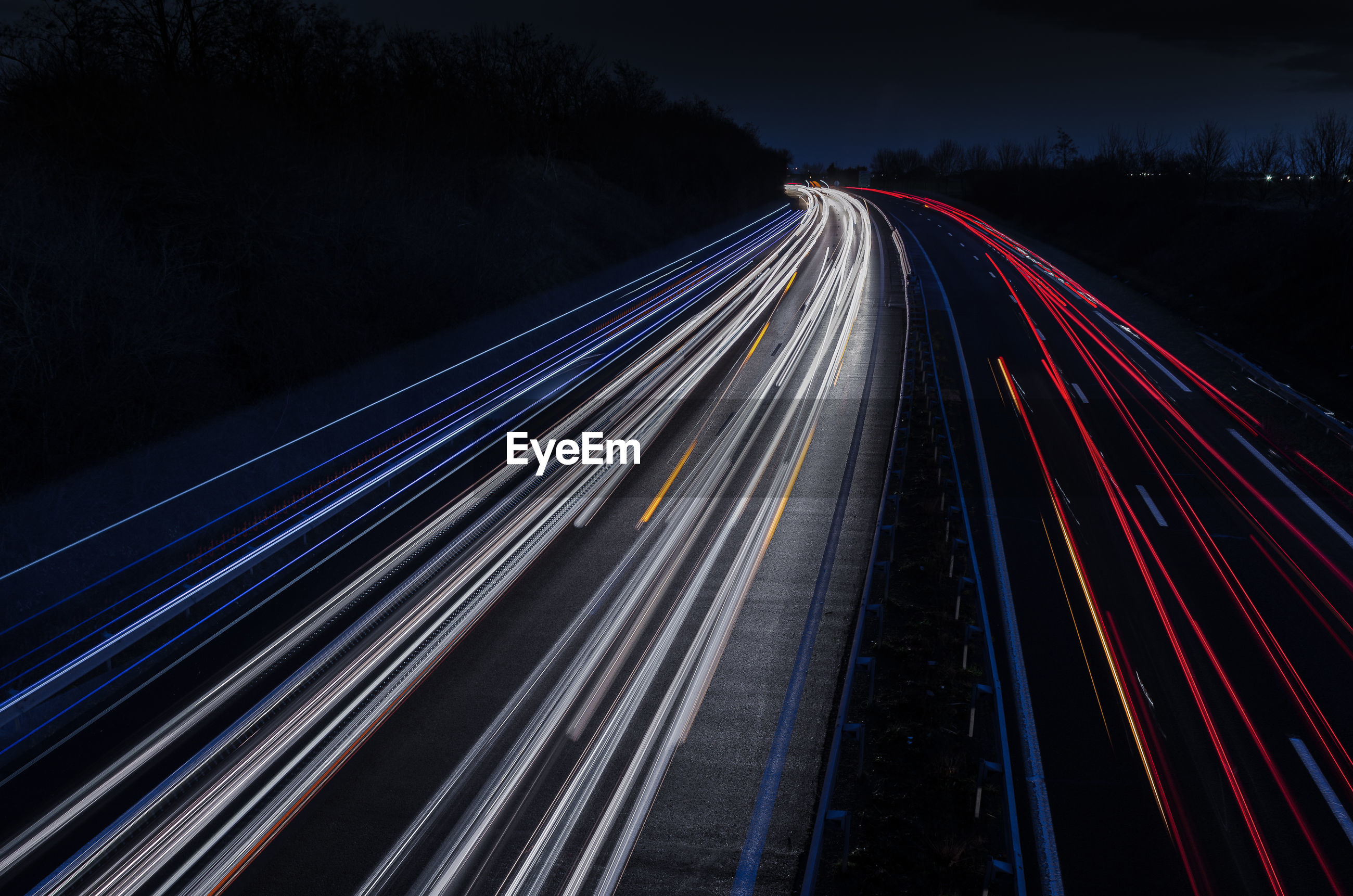 HIGH ANGLE VIEW OF LIGHT TRAILS ON ROAD DURING NIGHT