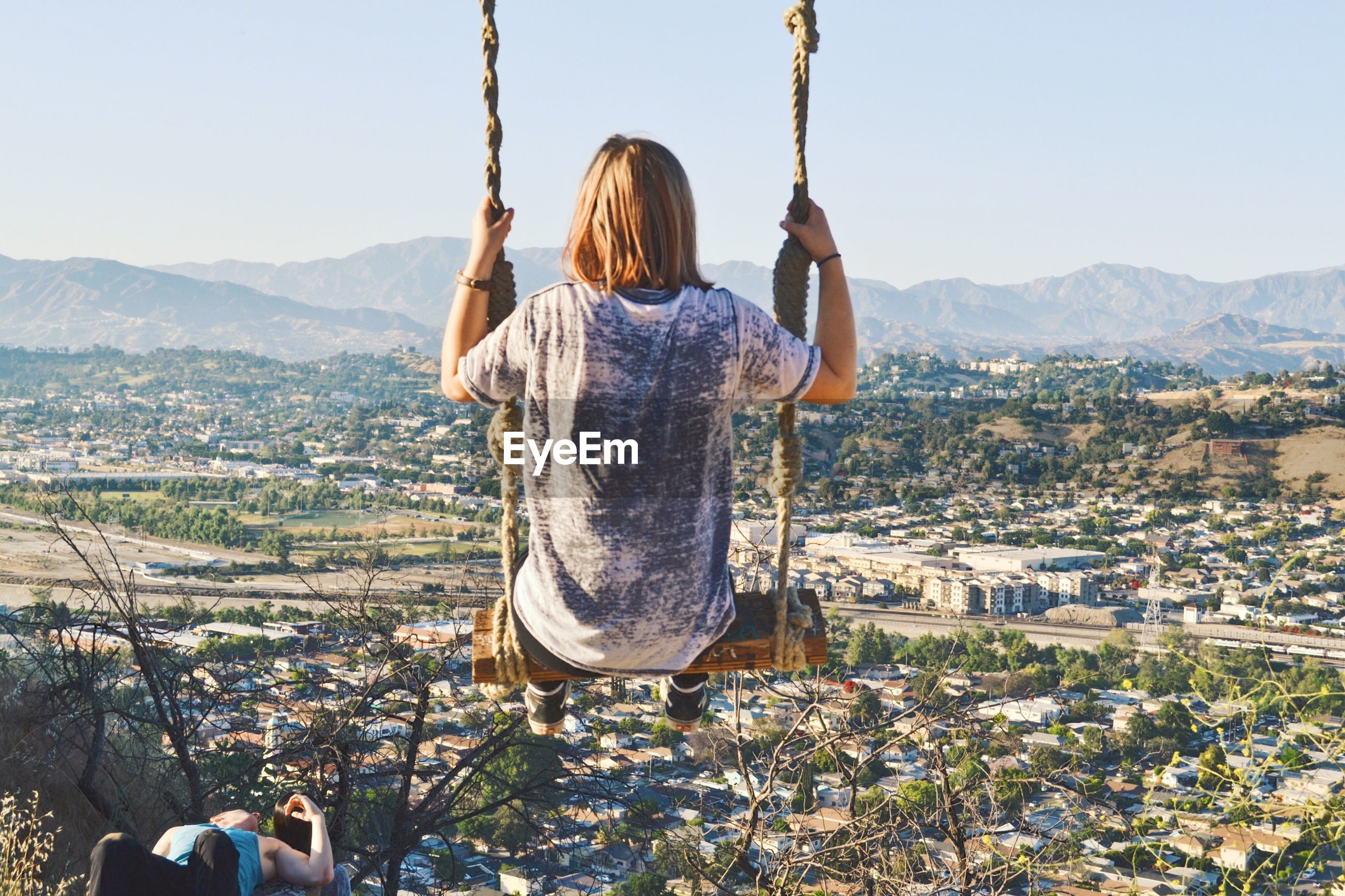 Rear view of woman sitting on swing against cityscape