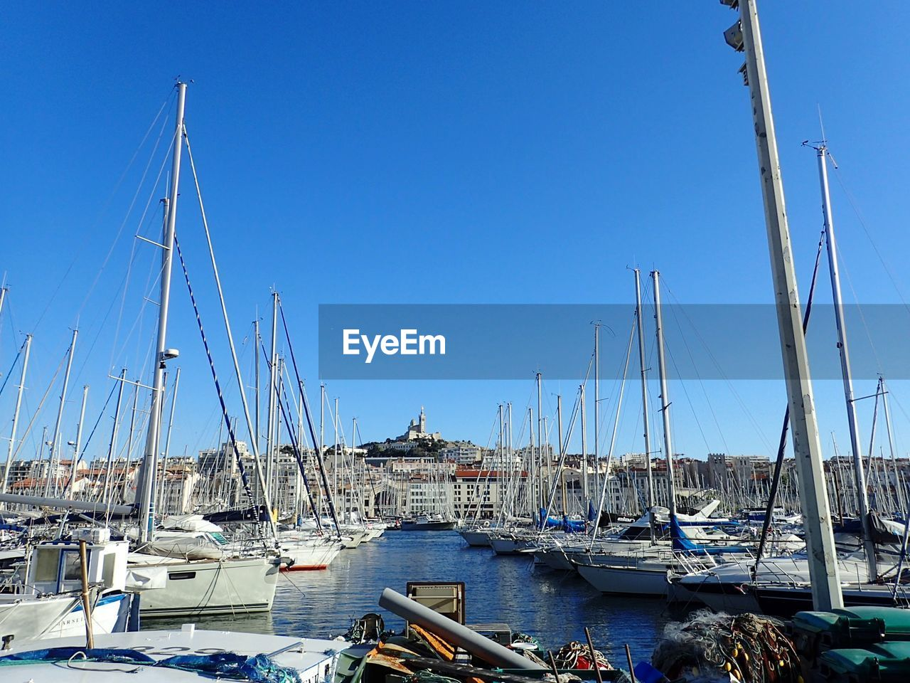 nautical vessel, moored, transportation, mast, mode of transport, sailboat, harbor, boat, blue, clear sky, day, no people, outdoors, large group of objects, marina, water, sunlight, sea, yacht, sky, nature, architecture