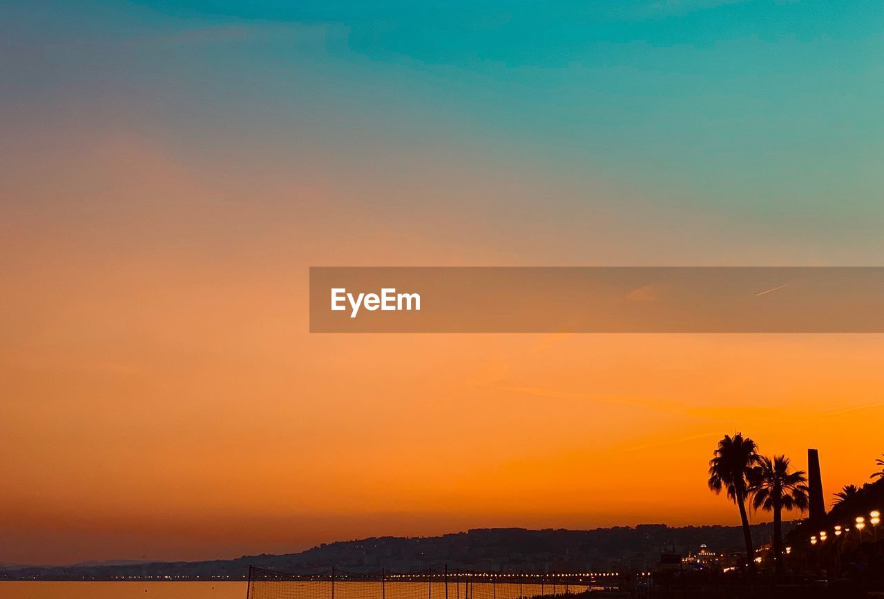 sunset, sky, orange color, scenics - nature, beauty in nature, nature, water, silhouette, tranquility, tree, tranquil scene, no people, copy space, sea, outdoors, idyllic, palm tree, architecture, non-urban scene