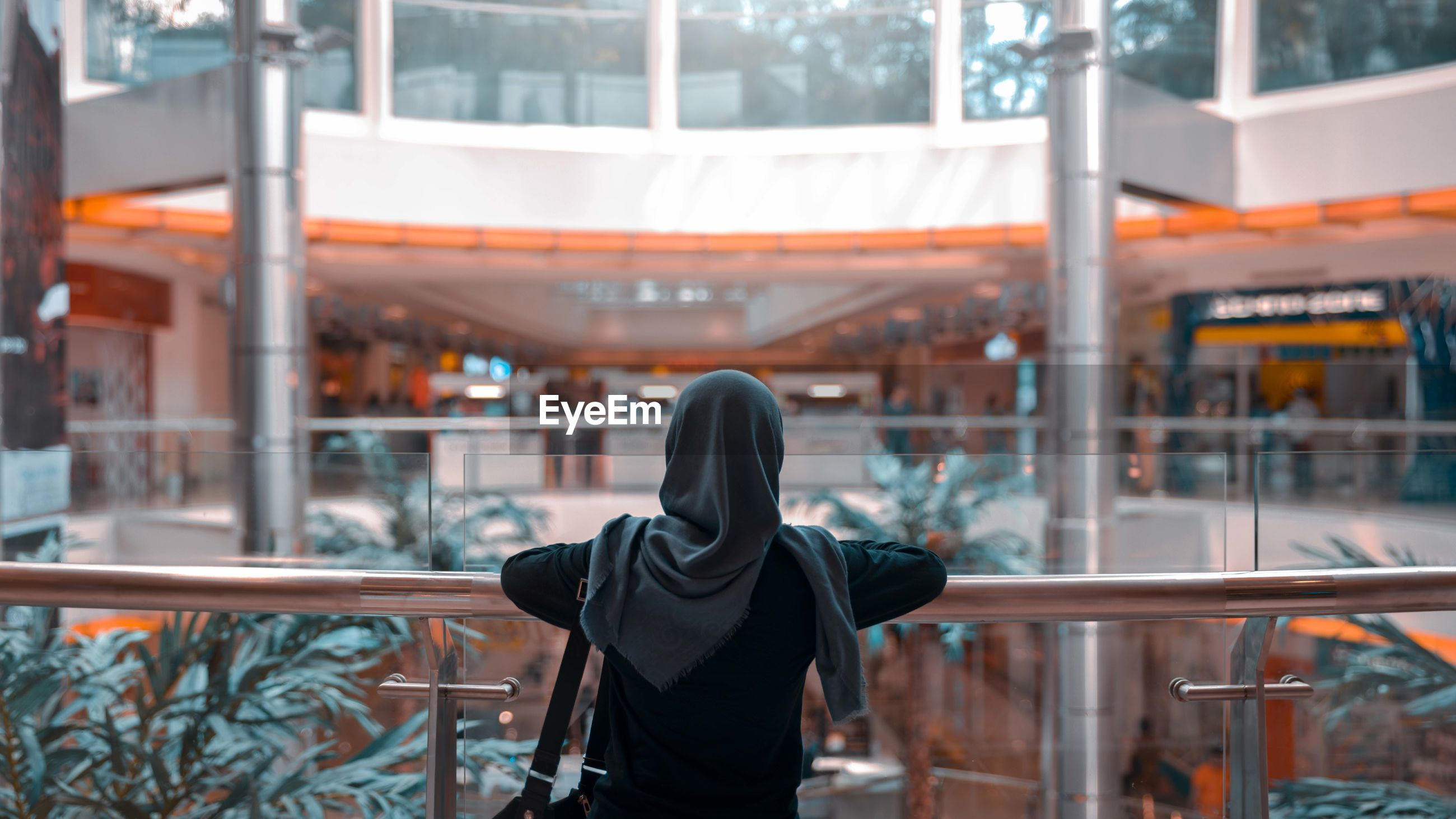 Rear view of woman in hijab standing at shopping mall