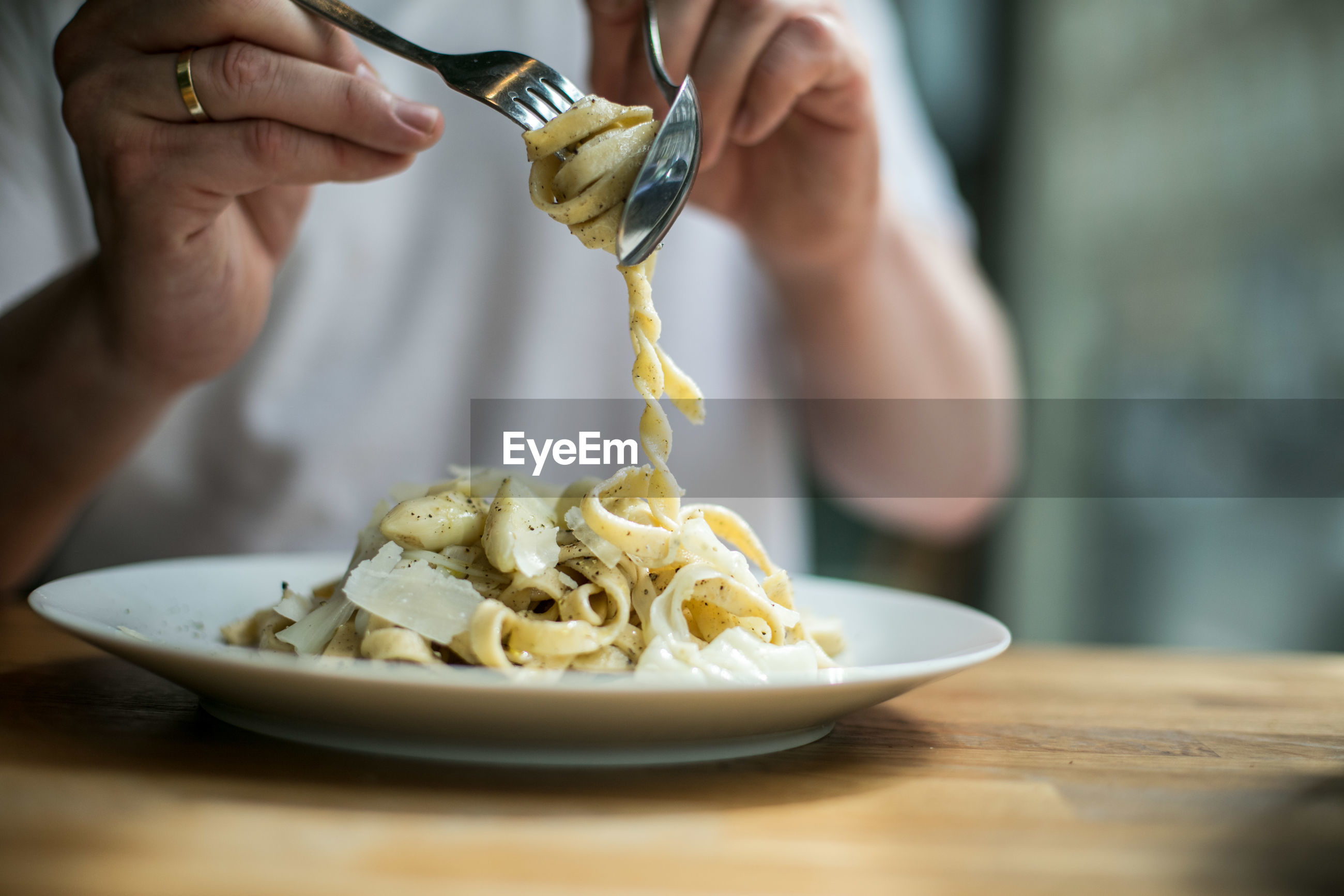 Midsection of person eating pasta