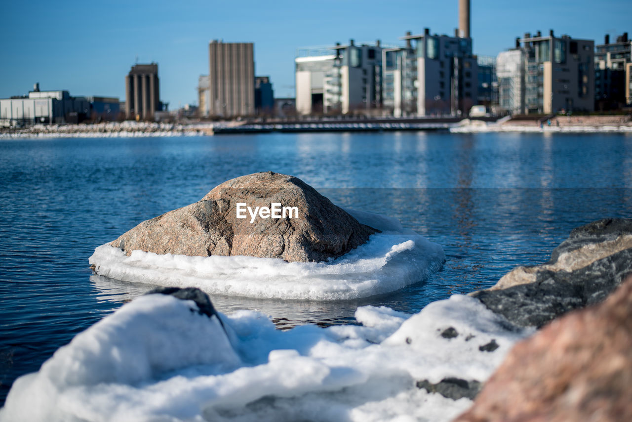Rock By Snow In River Against Skyscrapers