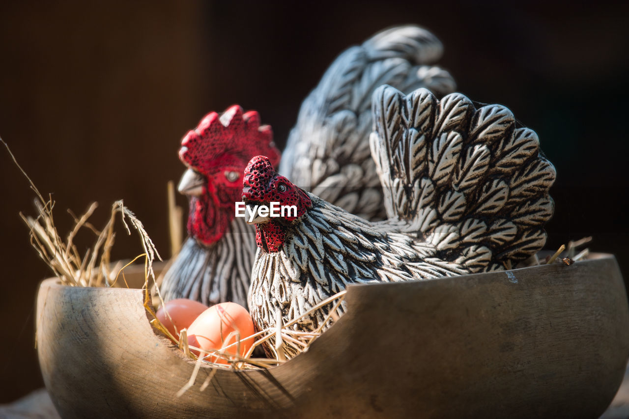 Clay hen and egg, molded from clay and through heat, in wood basket.