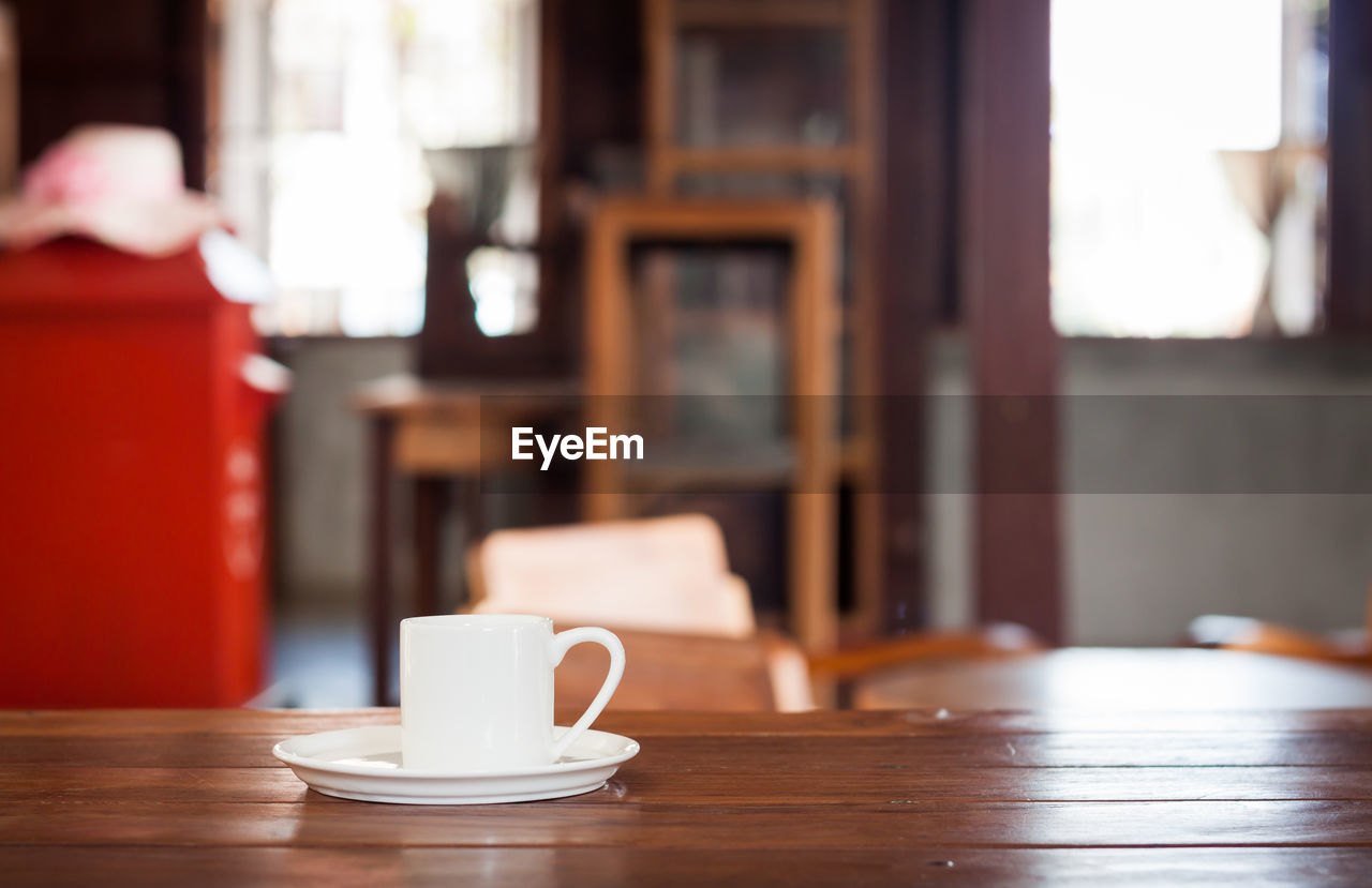 coffee cup, coffee - drink, table, drink, cafe, focus on foreground, cup, saucer, food and drink, refreshment, indoors, wood - material, restaurant, close-up, no people, day, freshness, mocha