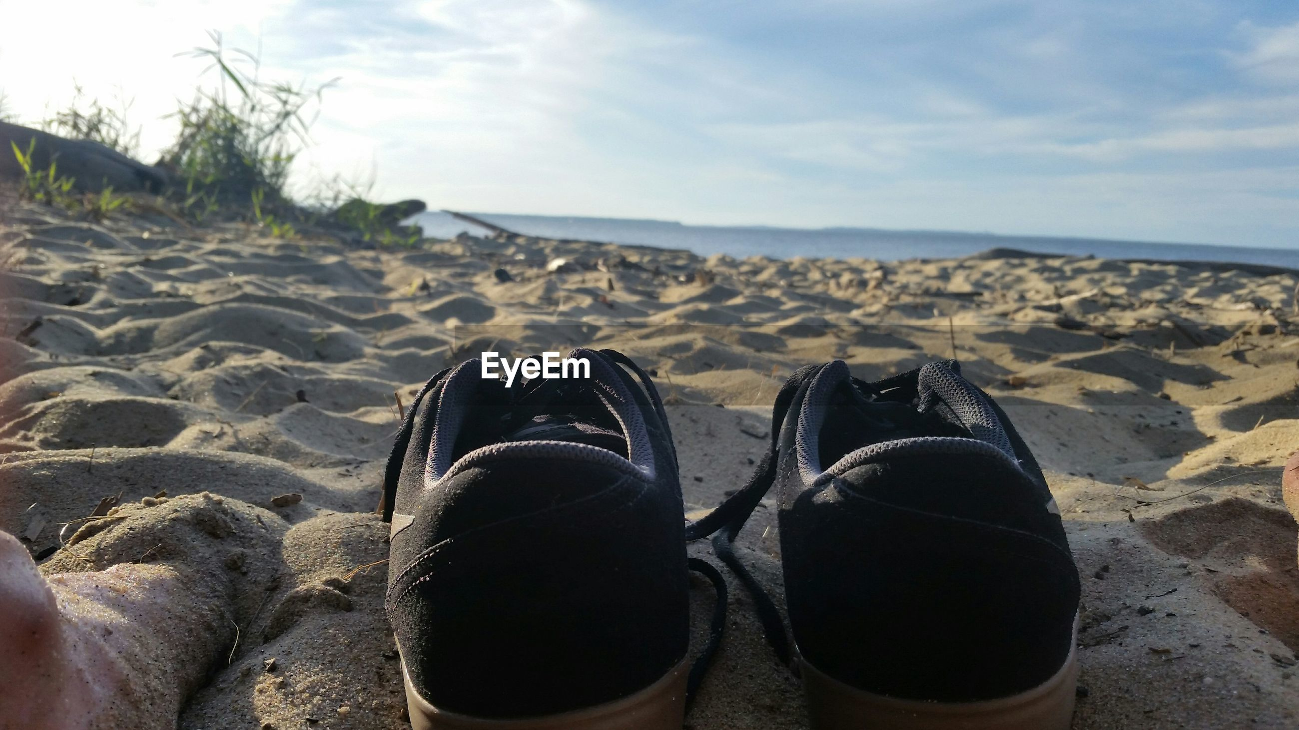 Low section of person with shoes at beach against sky